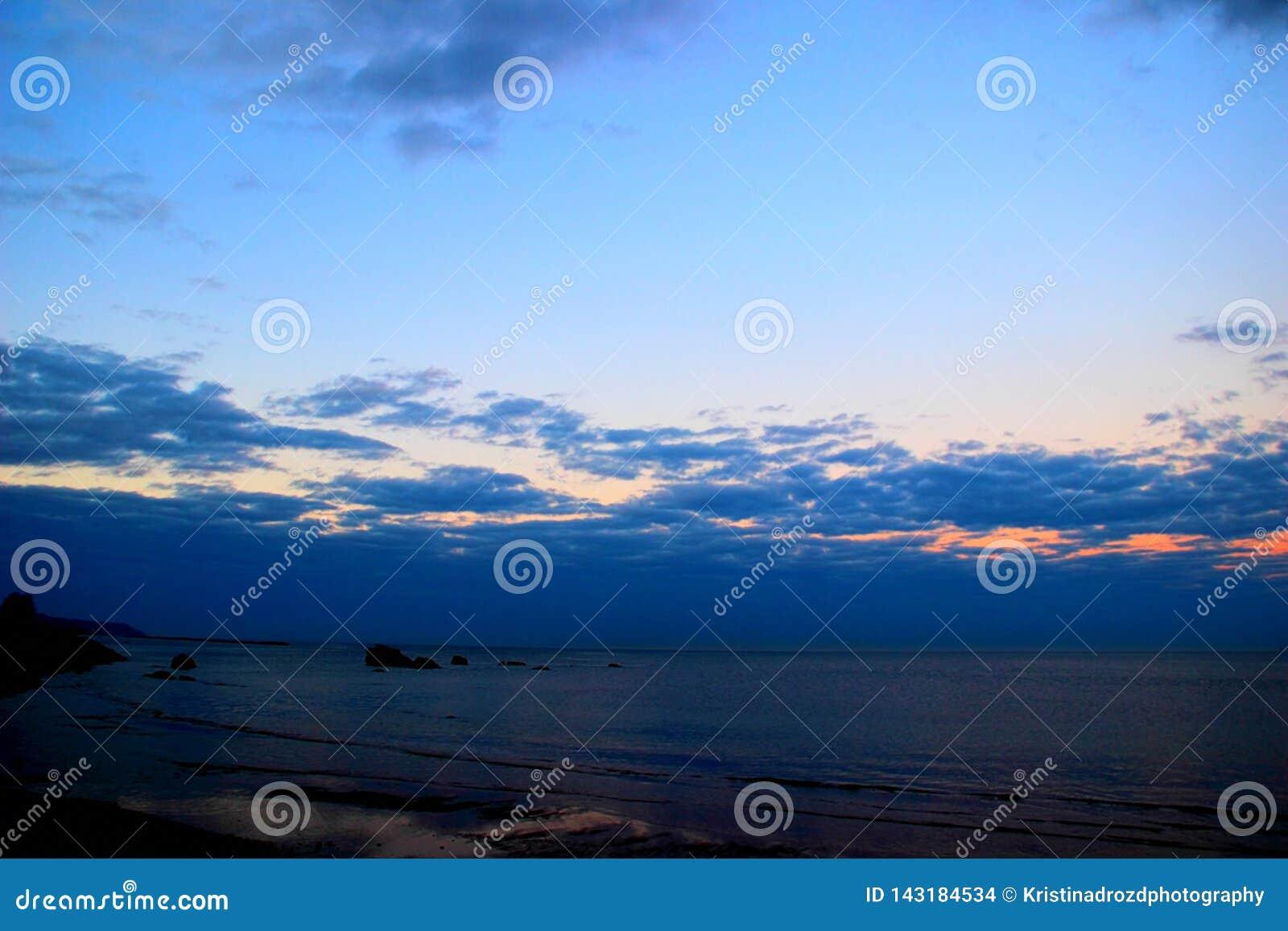 Diep blauwe bewolkte hemel over het overzees