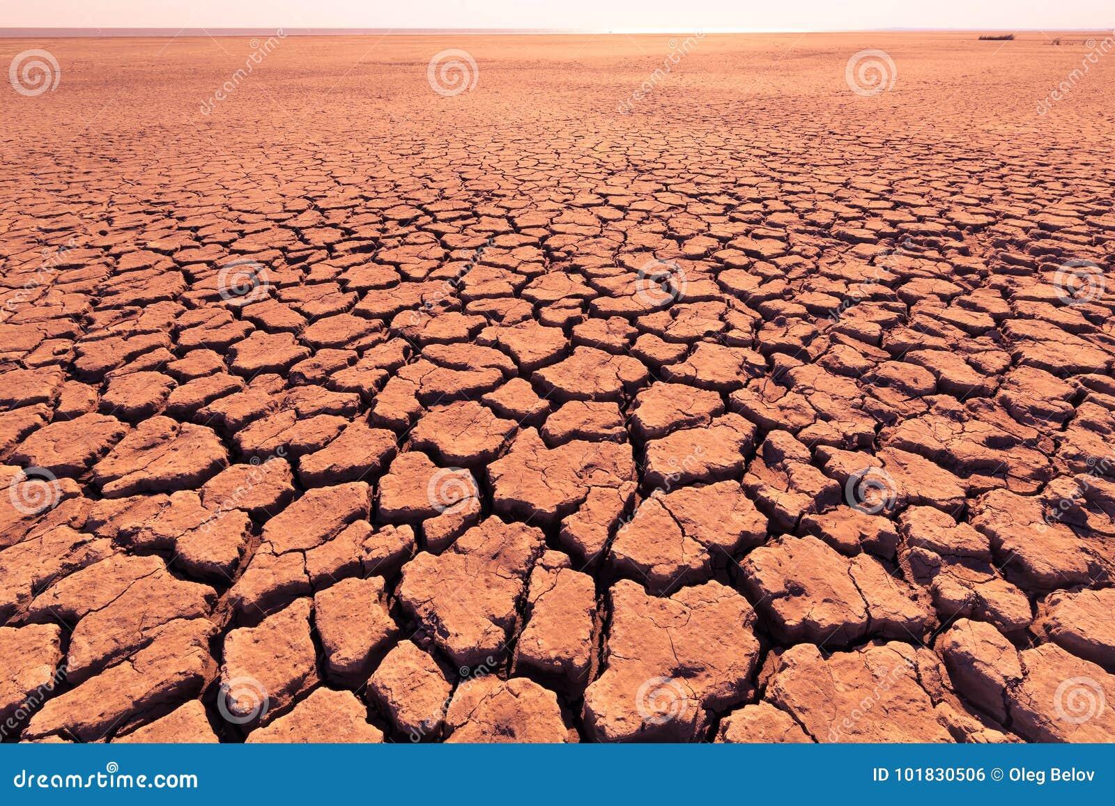 Diepe barsten in het rode land als symbool van hete klimaat en droogte