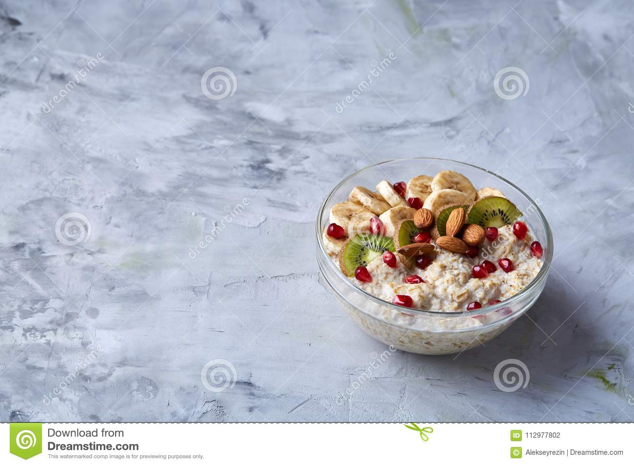 Diet breakfast oatmeal with fruits, bowl and spoon with oat flakes, selective focus, close-up