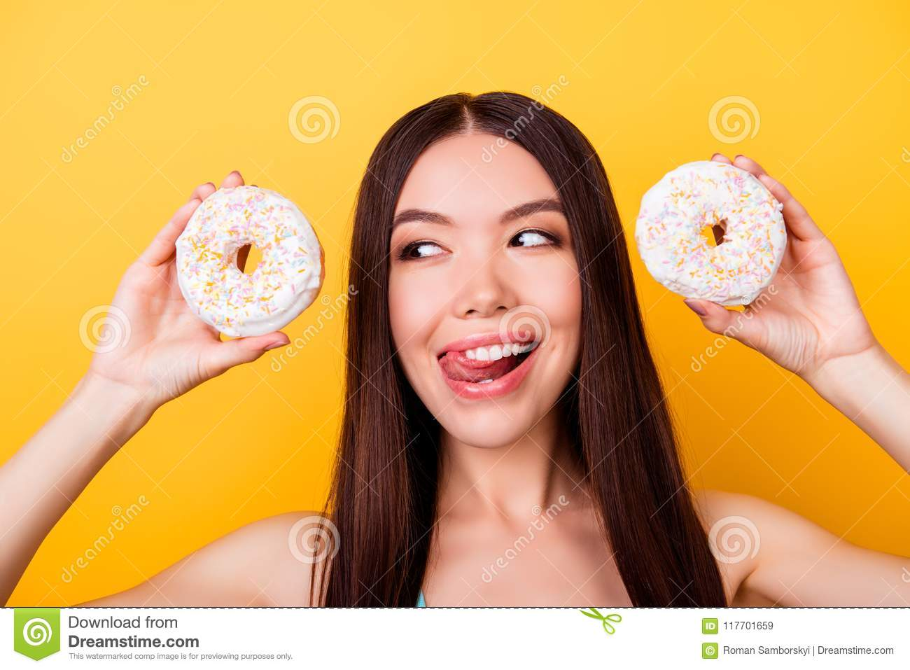Diet and calories concept. Close up portrait of happy asian girl looking on donutes with tounge out, so playful and hungry. Pretty