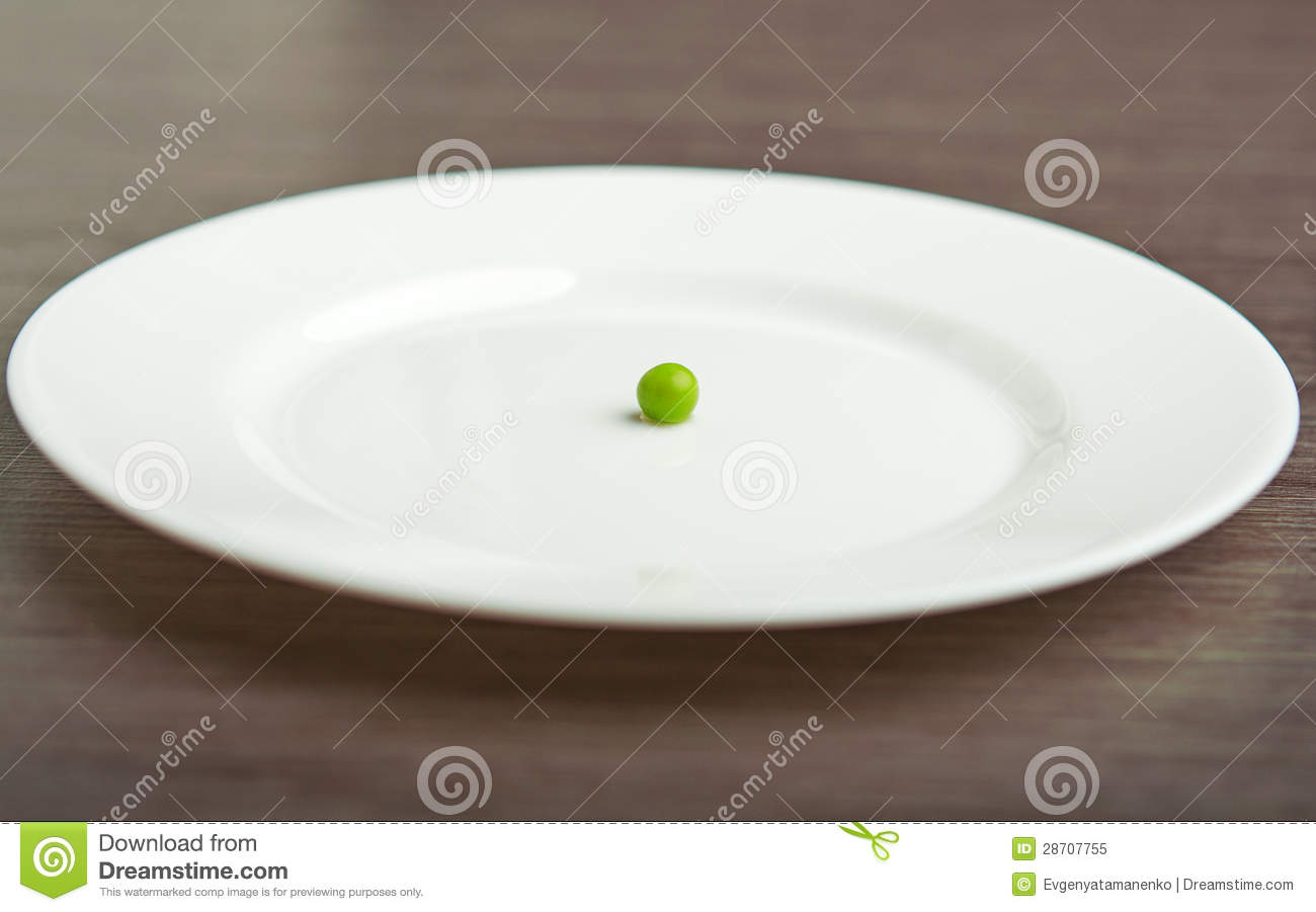 diet concept one pea on an empty white plate royalty free