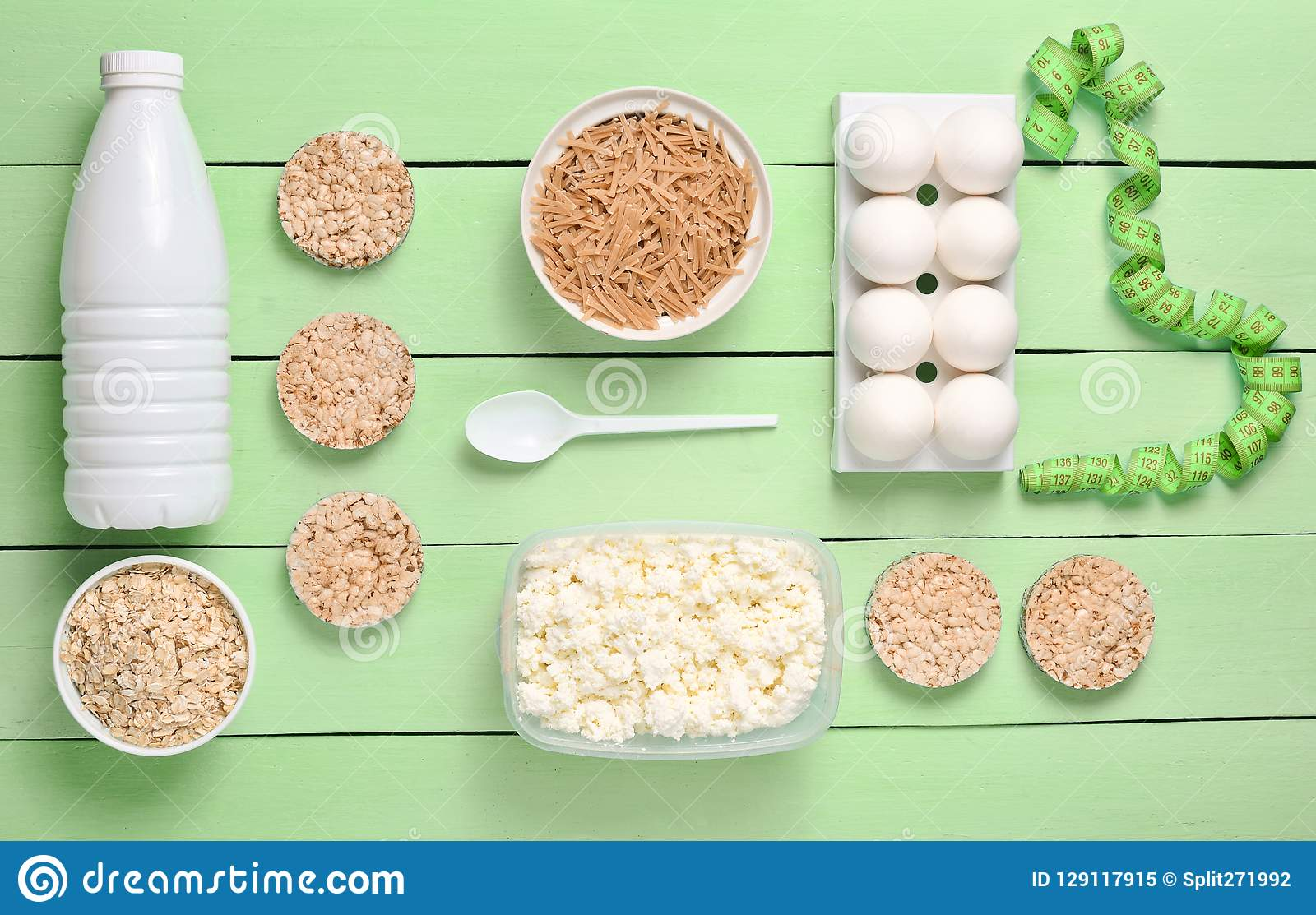 Diet, healthy food. Bottle of yogurt, crispy round bread, buckwheat noodles, oatmeal, cottage cheese, egg tray on a blue wooden b