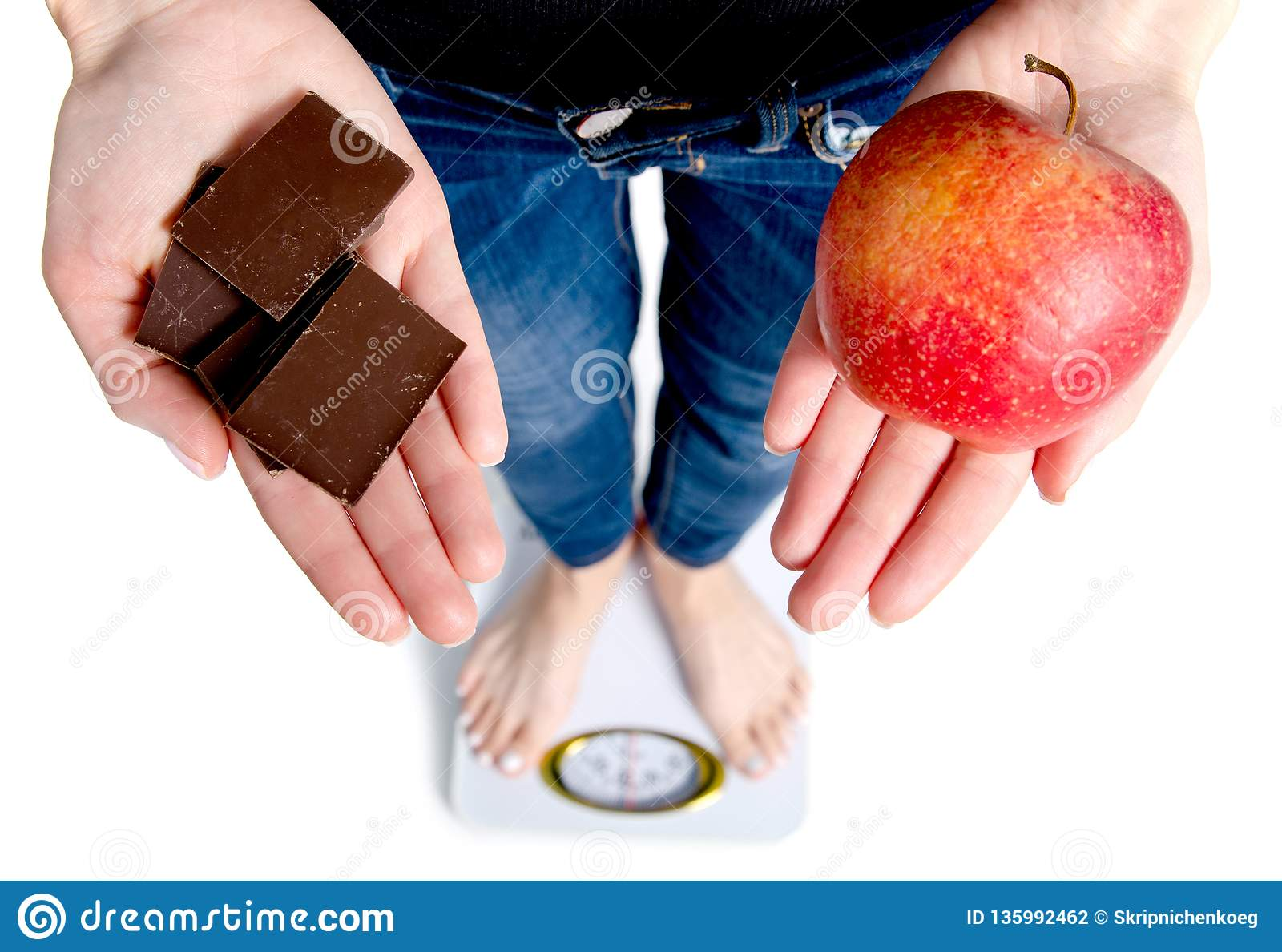 Diet. Woman Measuring Body Weight On Weighing Scale Holding chocolate and apple.