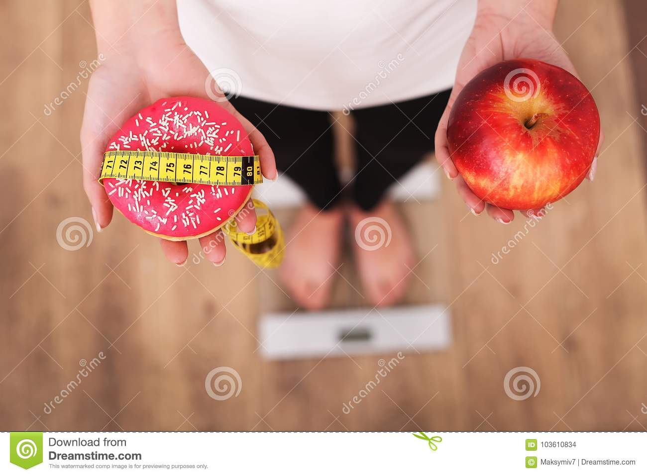 Diet. Woman Measuring Body Weight On Weighing Scale Holding Donut and apple. Sweets Are Unhealthy Junk Food. Dieting, Healthy Eati