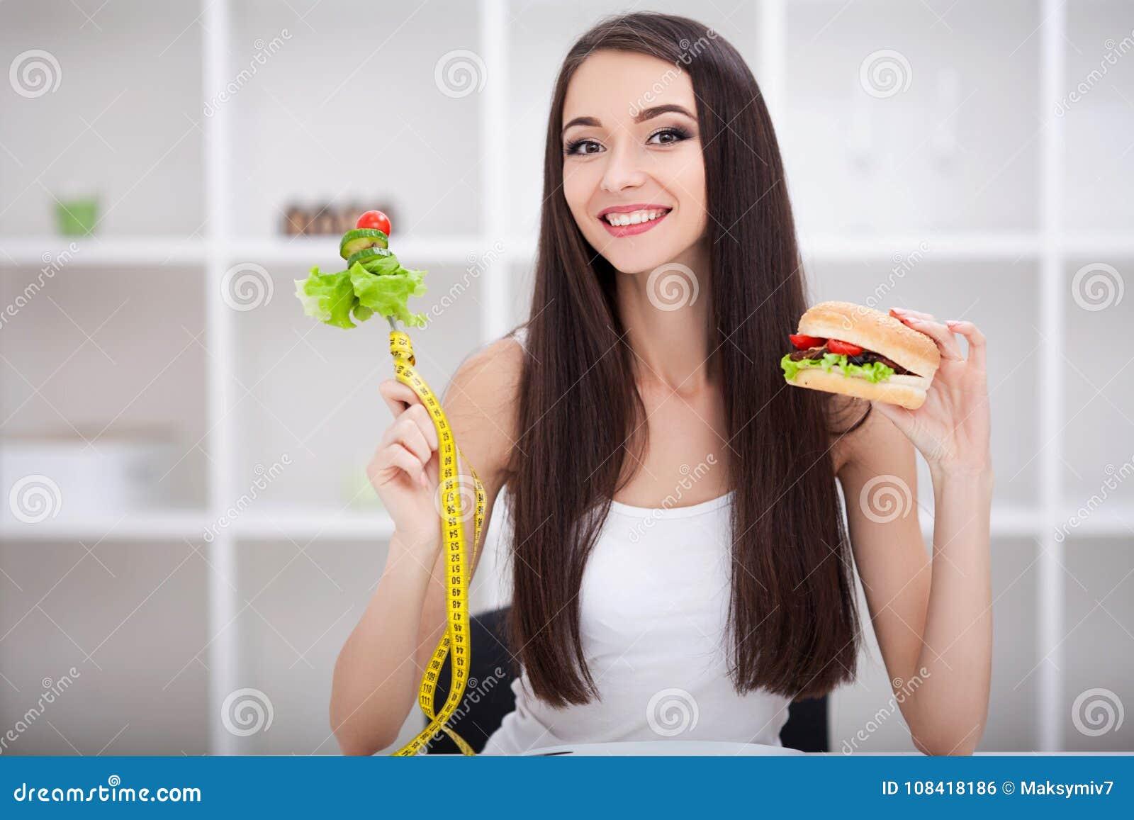 Dieta Conceito de dieta Escolha da menina saudável contra a comida lixo