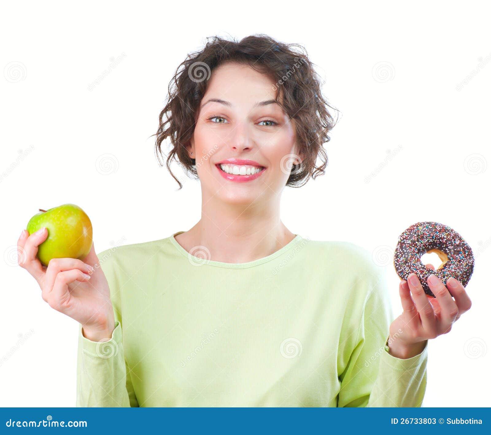 Dieta. Donna che sceglie fra la frutta e la ciambella