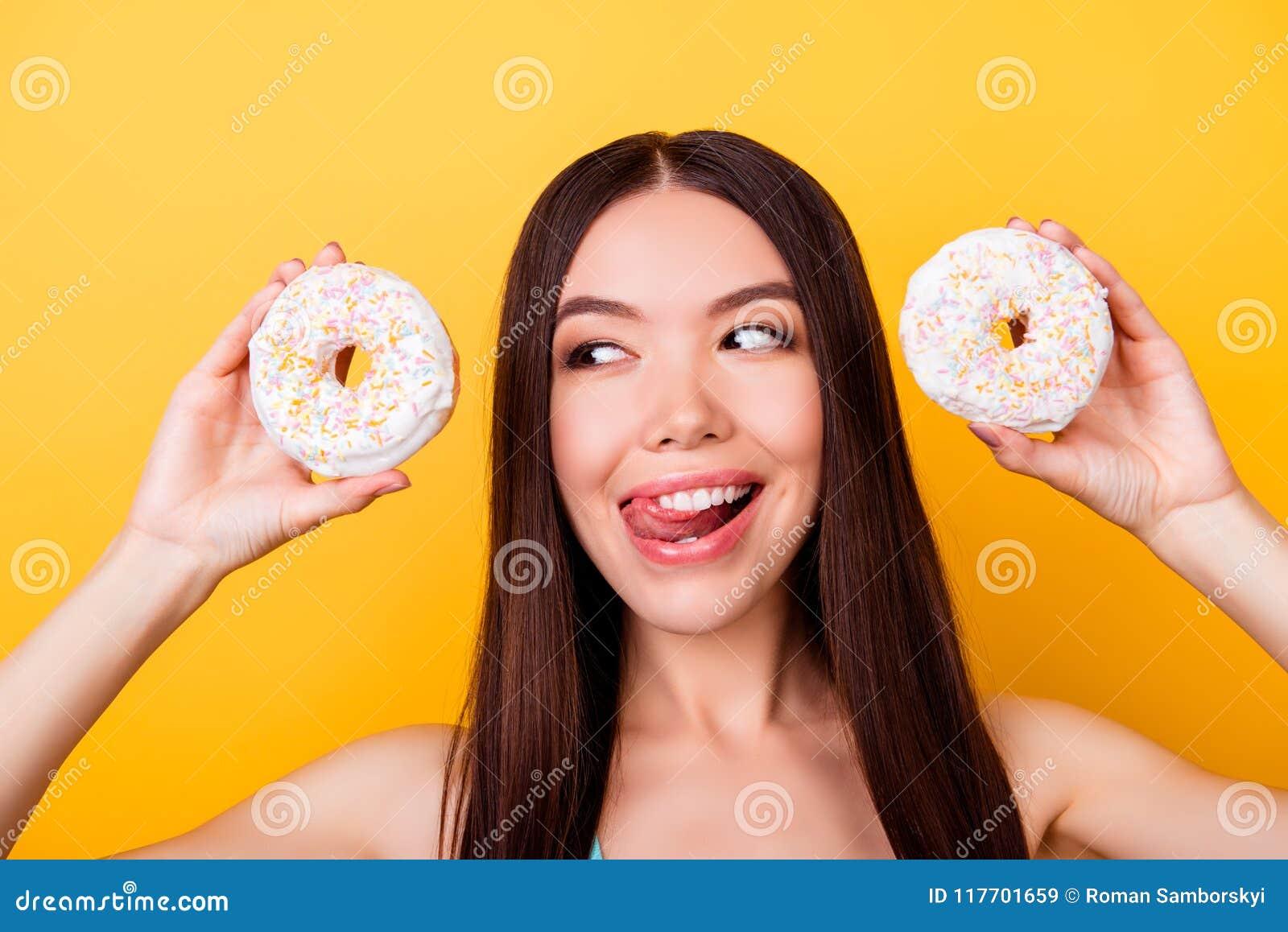 Dieta e calorias do conceito Feche acima do retrato da menina asiática feliz que olha em donutes com tounge para fora, tão brinca