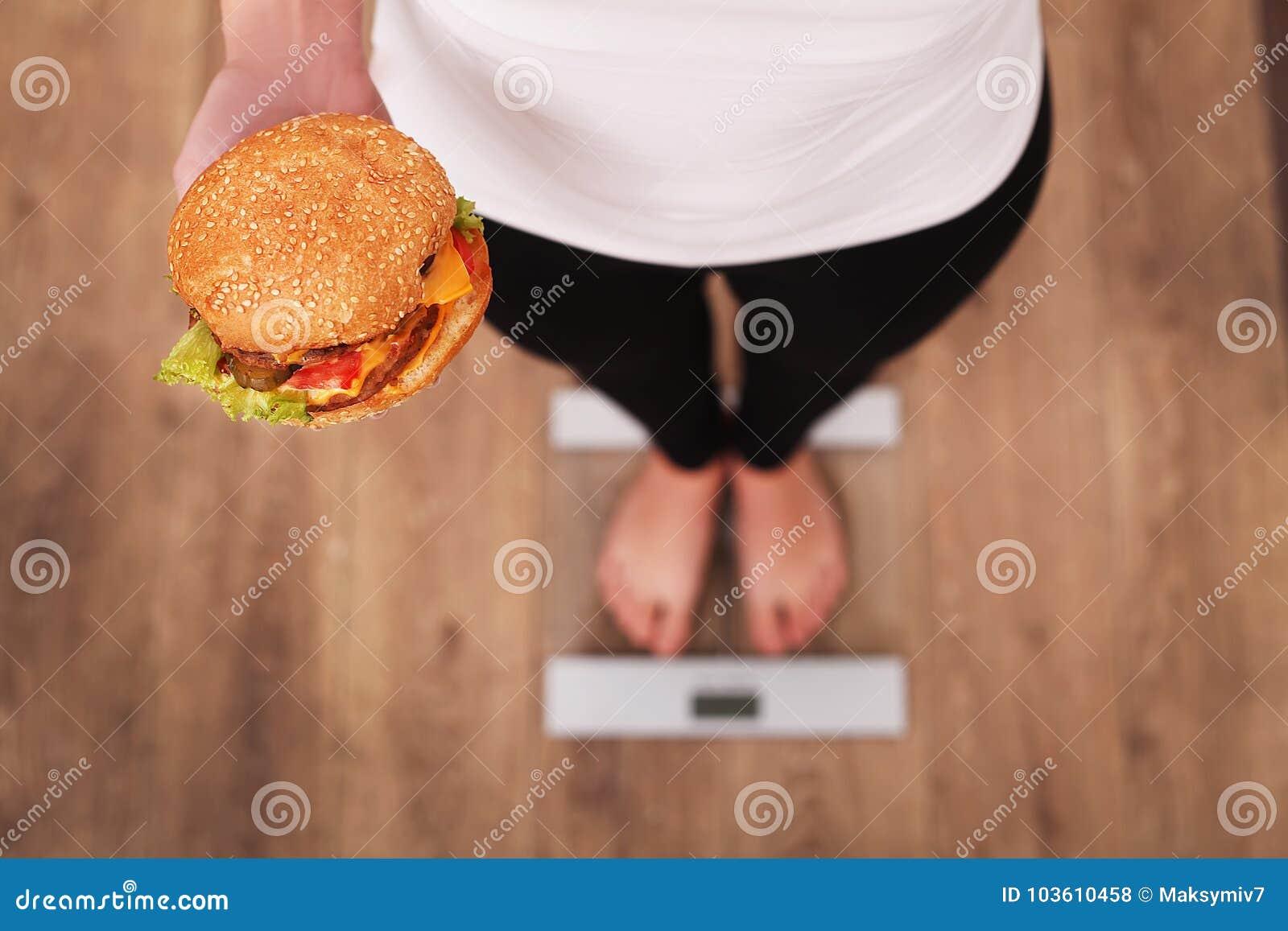 Dieta Peso corporal de medição da mulher na escala de peso que guarda o hamburguer e a maçã Os doces são comida lixo insalubre Fa