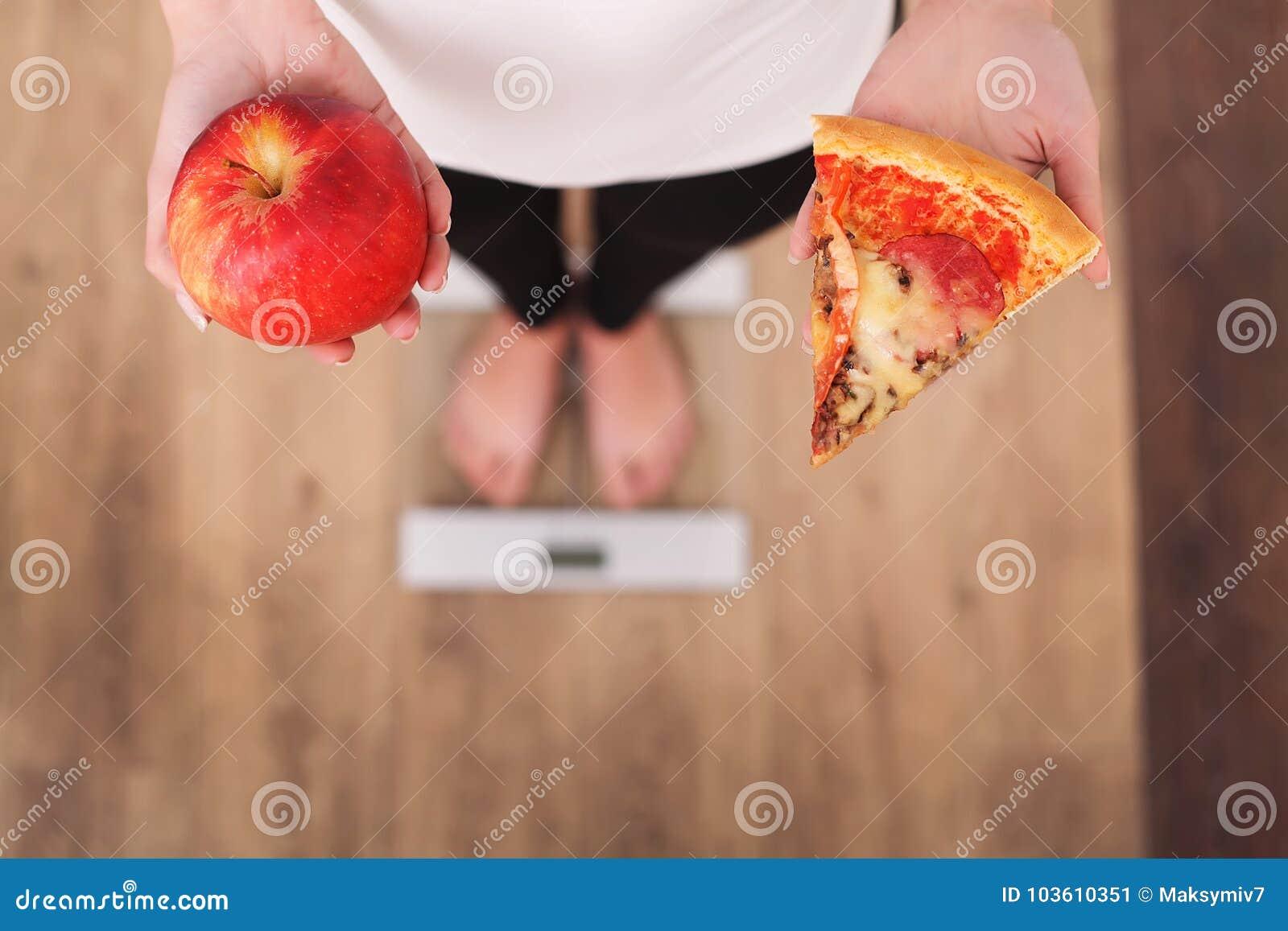 Dieta Peso corporal de medição da mulher na escala de peso que guarda a pizza Os doces são comida lixo insalubre Fazendo dieta, c