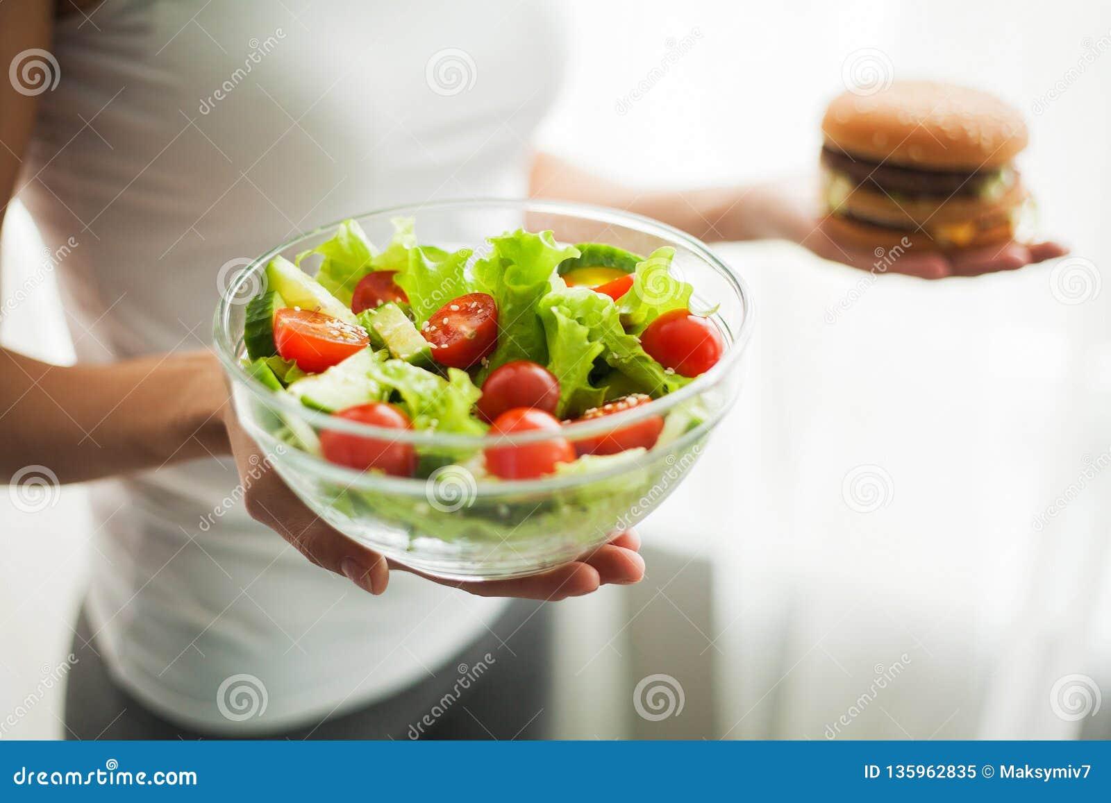 Dieta Peso corporal de medição da mulher no hamburguer e no Salat da terra arrendada da escala de peso Os doces são comida lixo i