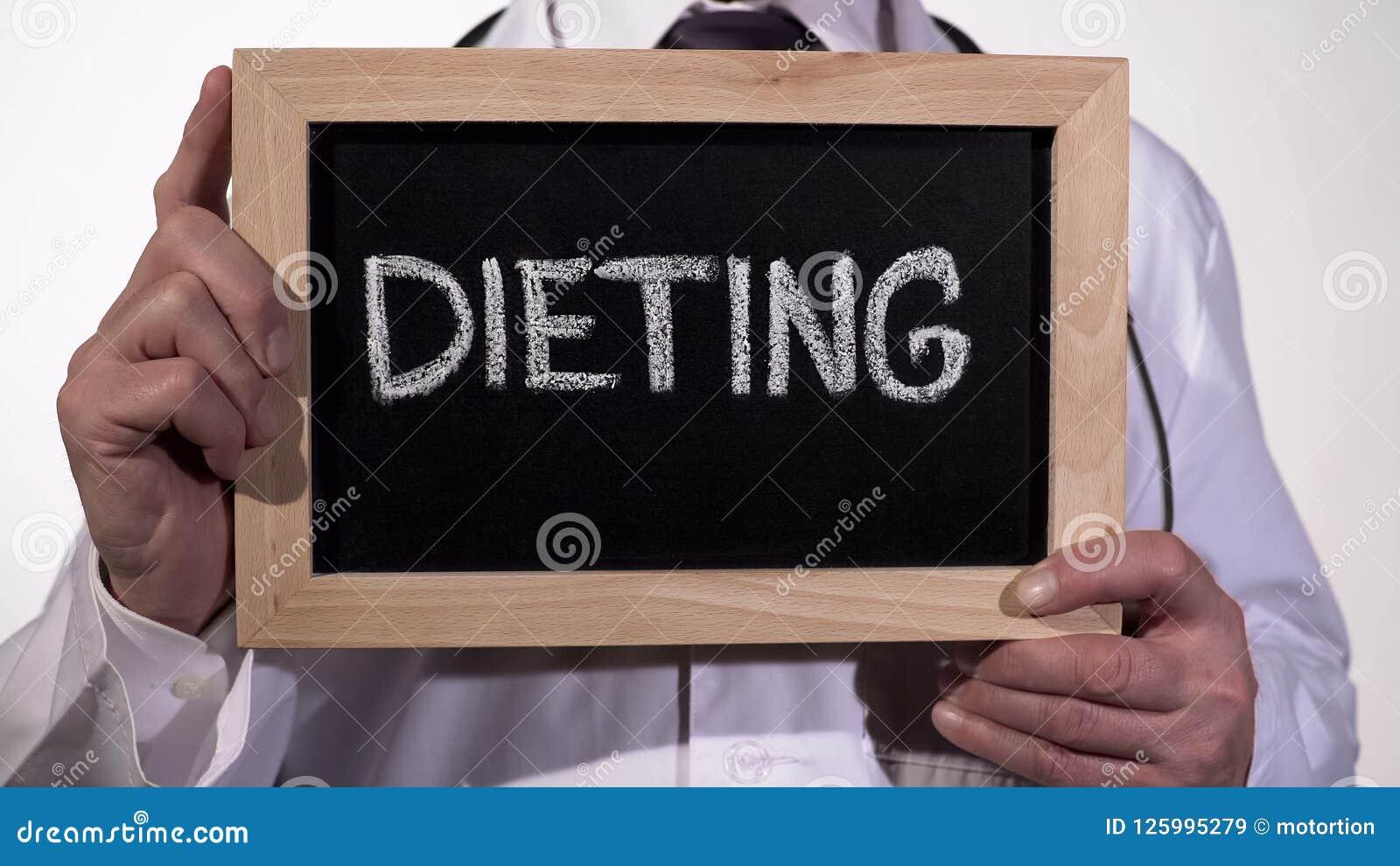 Dieting written on blackboard in doctor hands, nutritionist recommendations