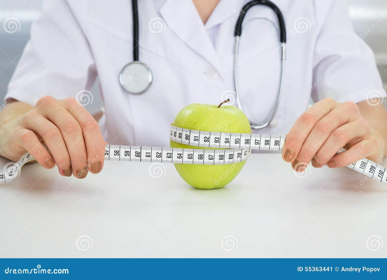 Dietista che misura mela verde