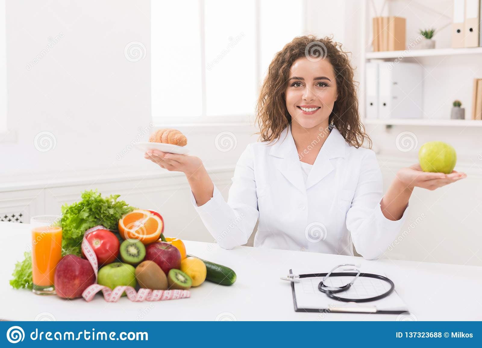 Dietista della donna che tiene frutta e croissant in mani