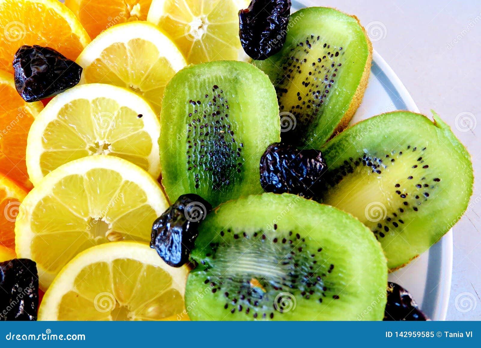 Différents fruits, oranges, citrons, kiwi et pruneaux