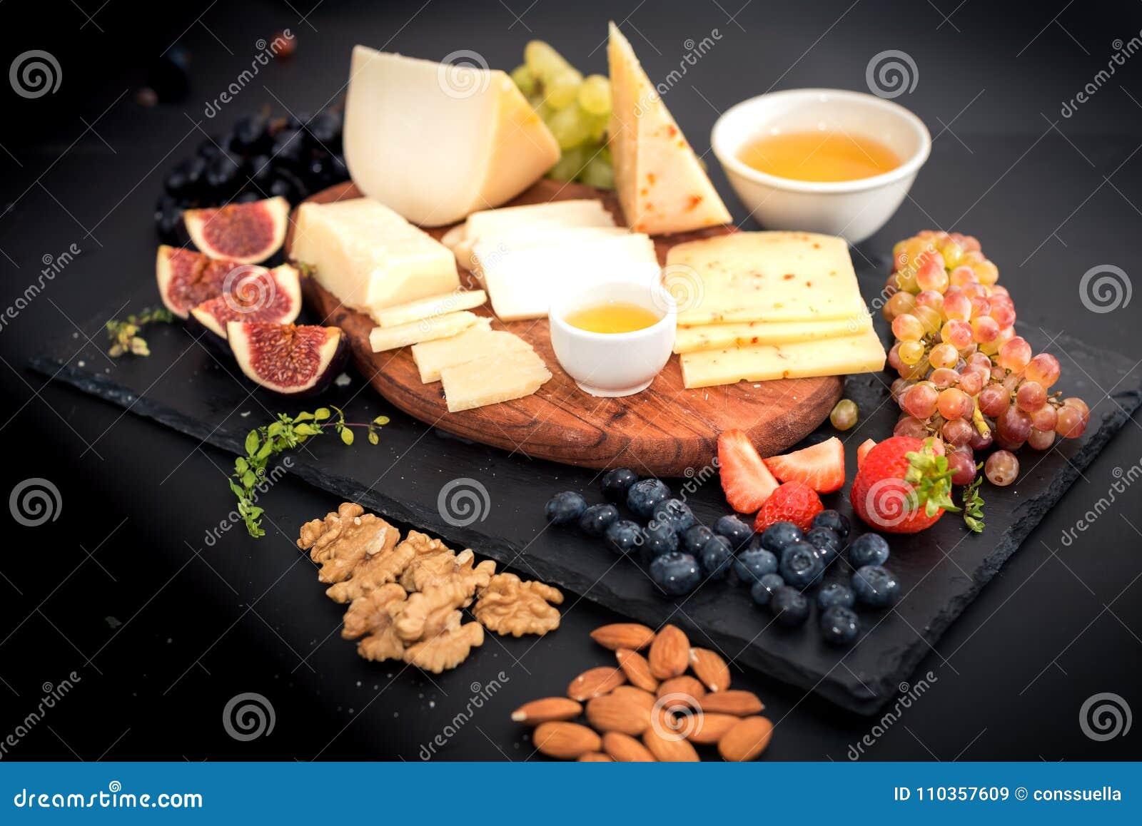 Différents genres de fromages, de miel, de figues, d écrous, de raisins, et de fruit sur une table Foyer sélectif Copiez l espace
