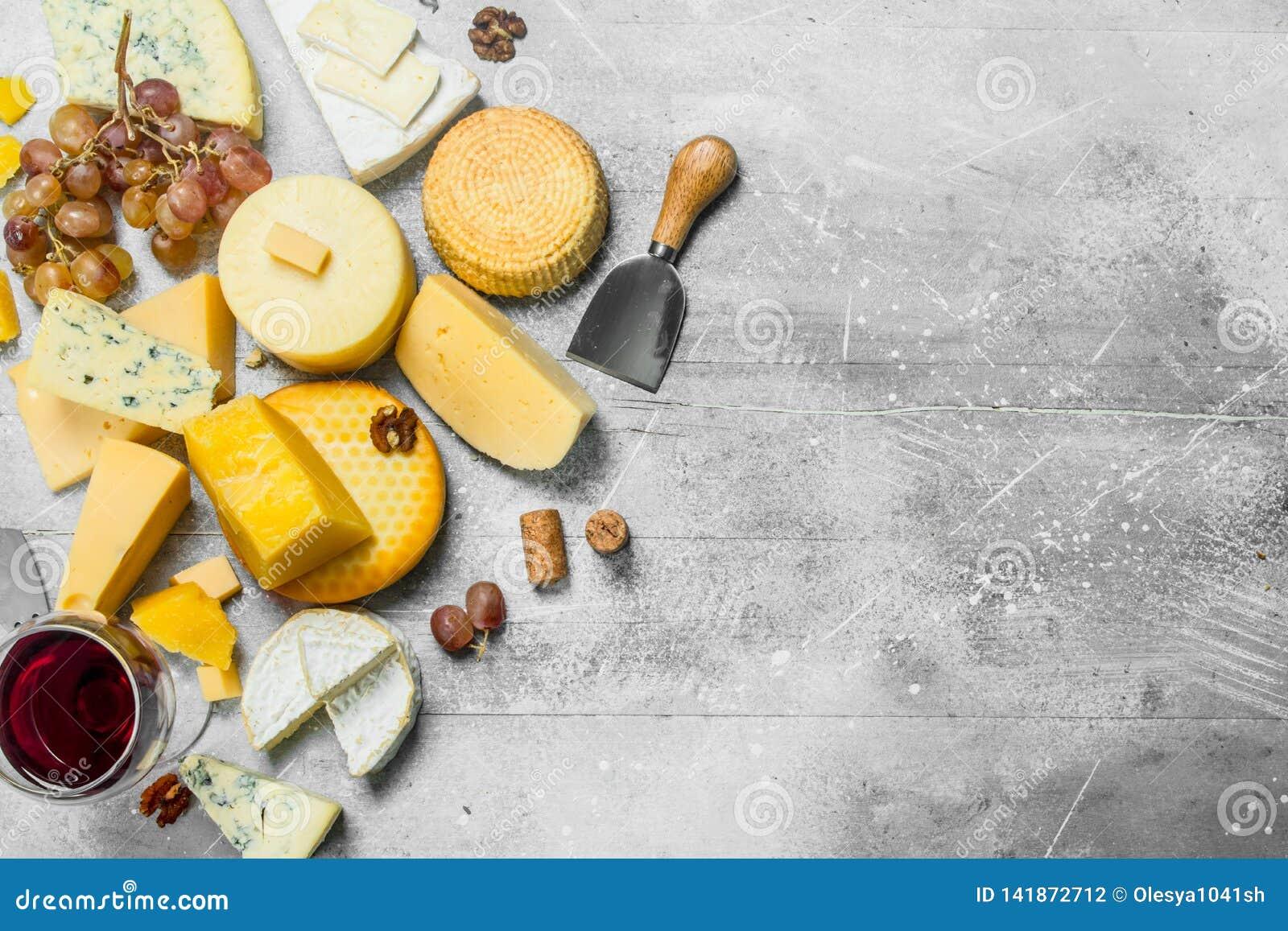 Différents types de fromage avec des raisins, des écrous et un verre de vin rouge