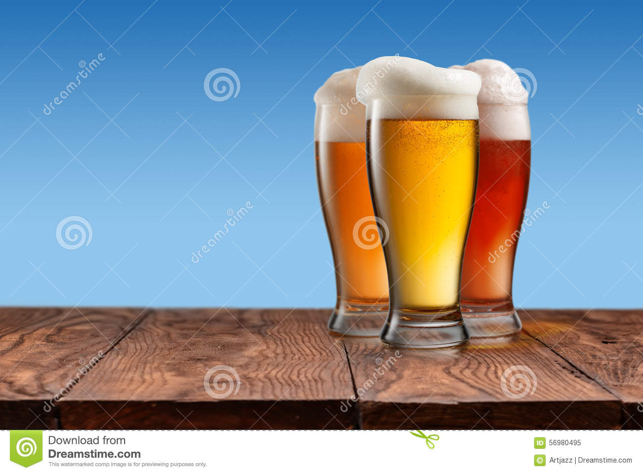 Different beer in glasses on wooden table and blue