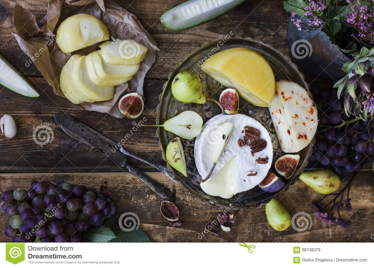 Different cheese, fresh fruits and garden flowers on old wooden background