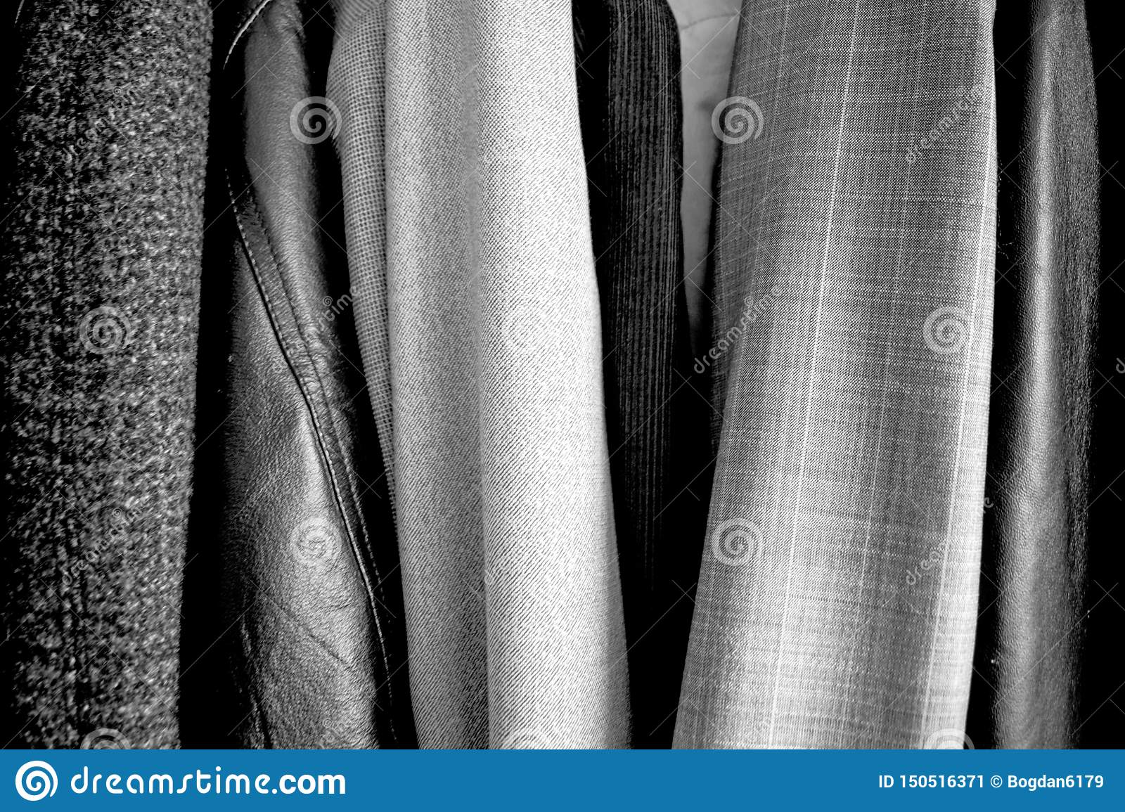 Different clothes placed in the wardrobe. Black and white. Good texture