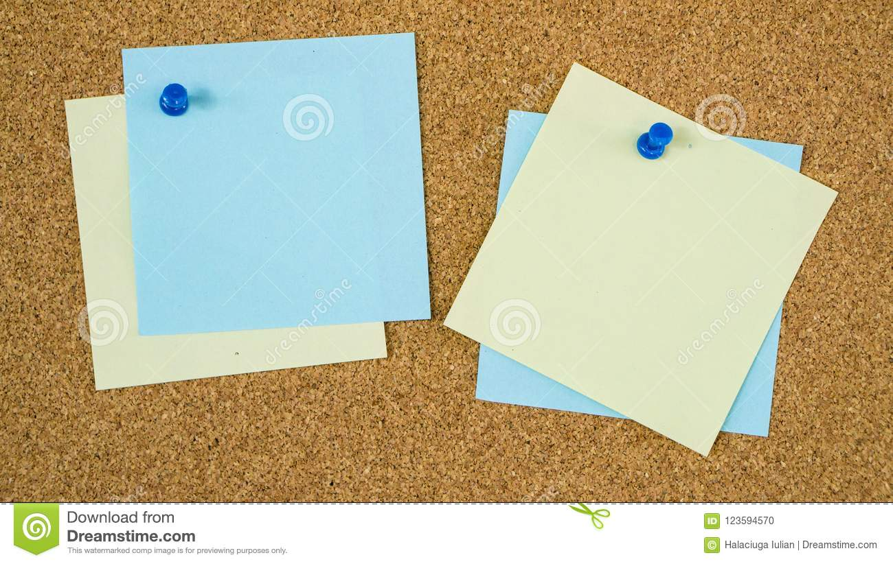 Different color post it notes pinned on cork board