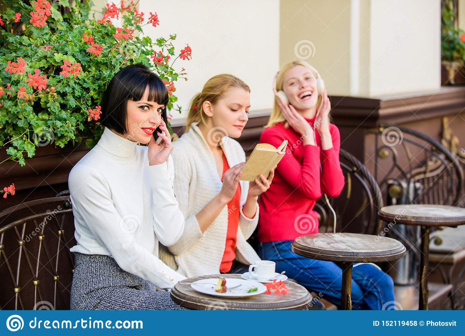 Different interests. Hobby and leisure. Group pretty women cafe terrace entertain themselves with reading speaking and