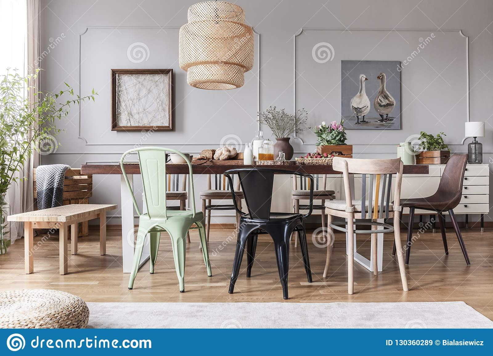 Different kid of chairs at table with flowers and food in rustic dining room interior with lamp and posters. Real photo