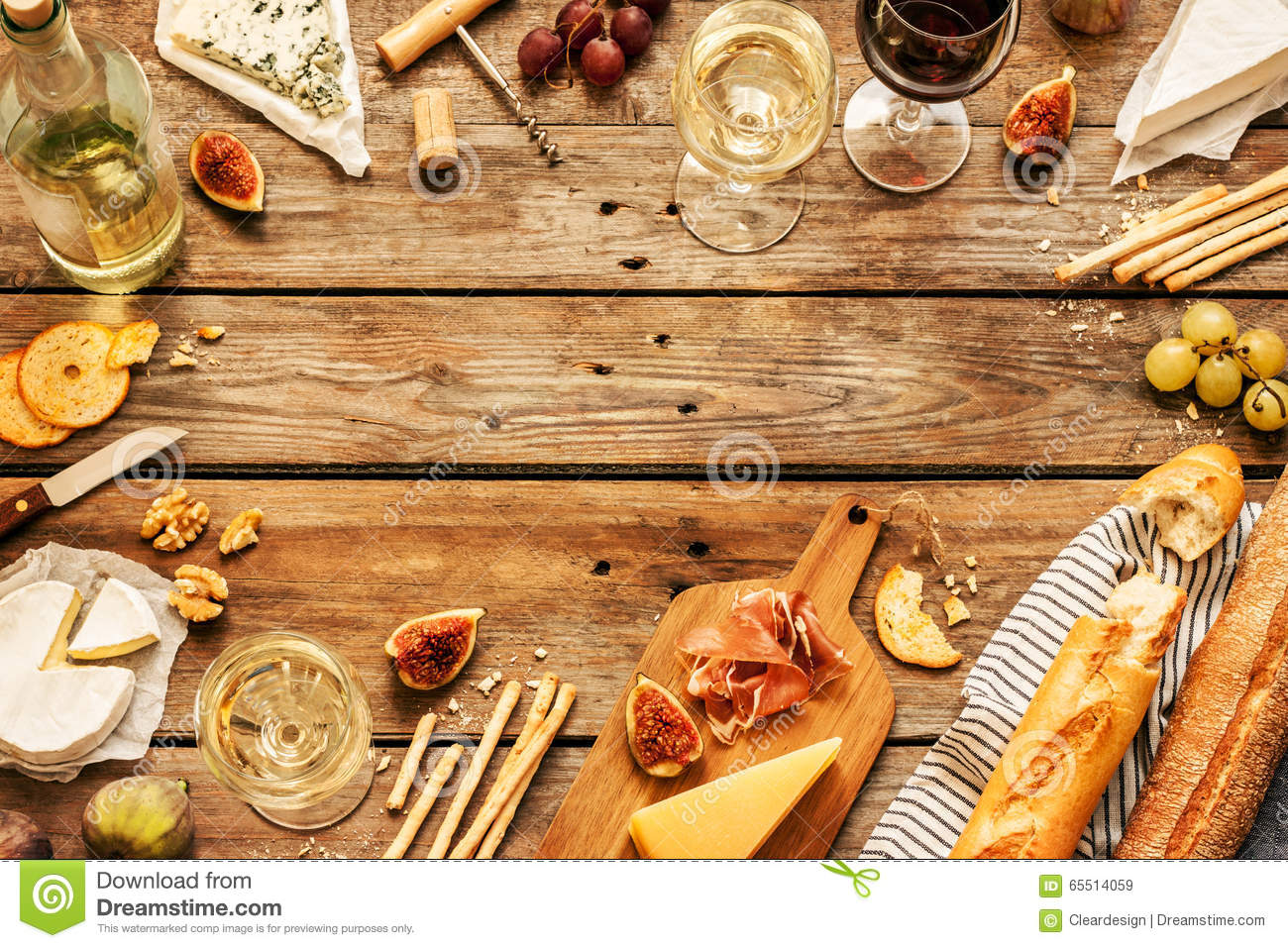 Different kinds of cheeses, wine, baguettes, fruits and snacks
