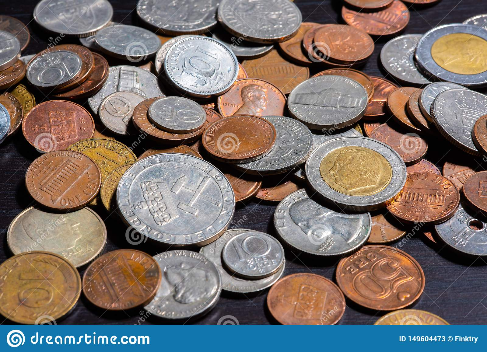 Different kinds of coins on a black table