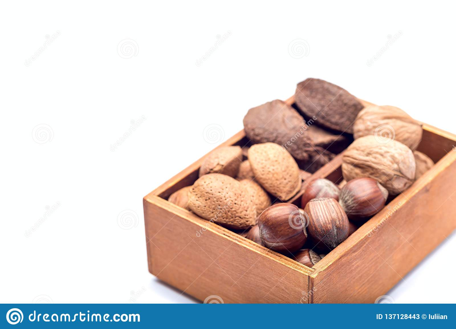 Different kinds of nuts in the shell: hazelnut, walnut, almond and brazil nuts in wooden box, isolated on a white background