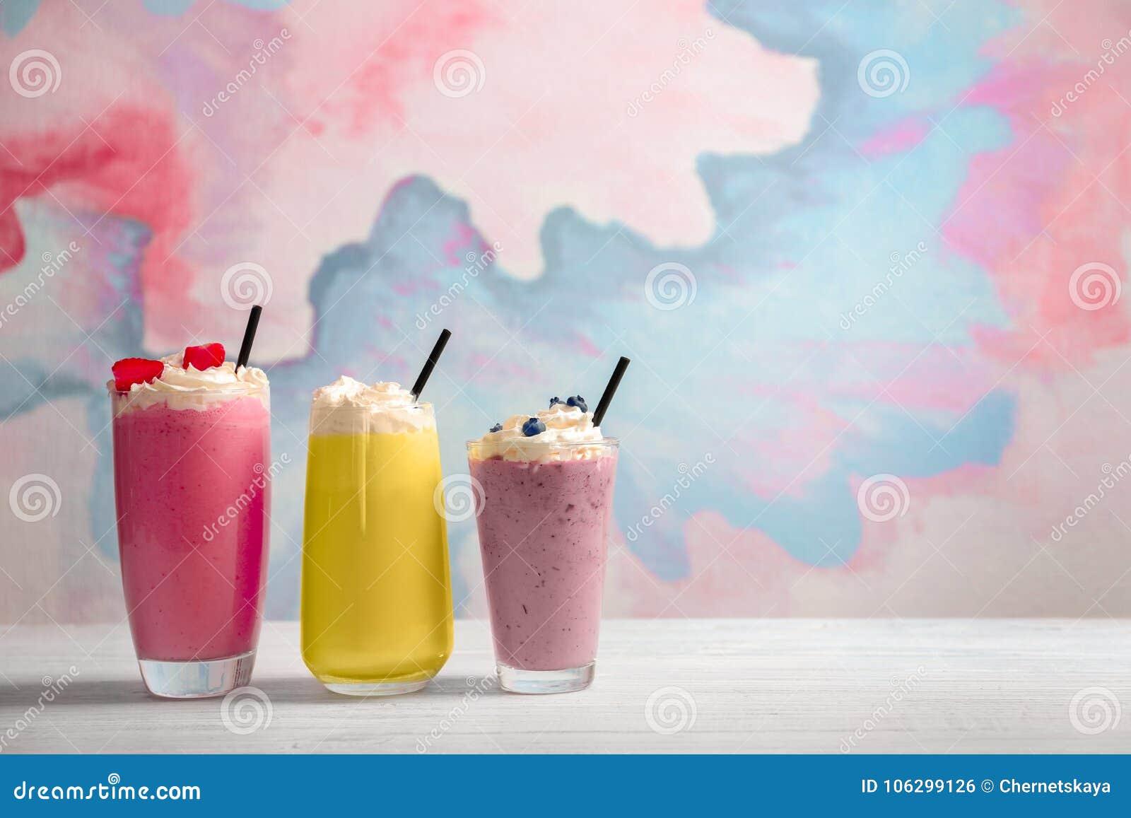 Different milkshakes in glasses on table