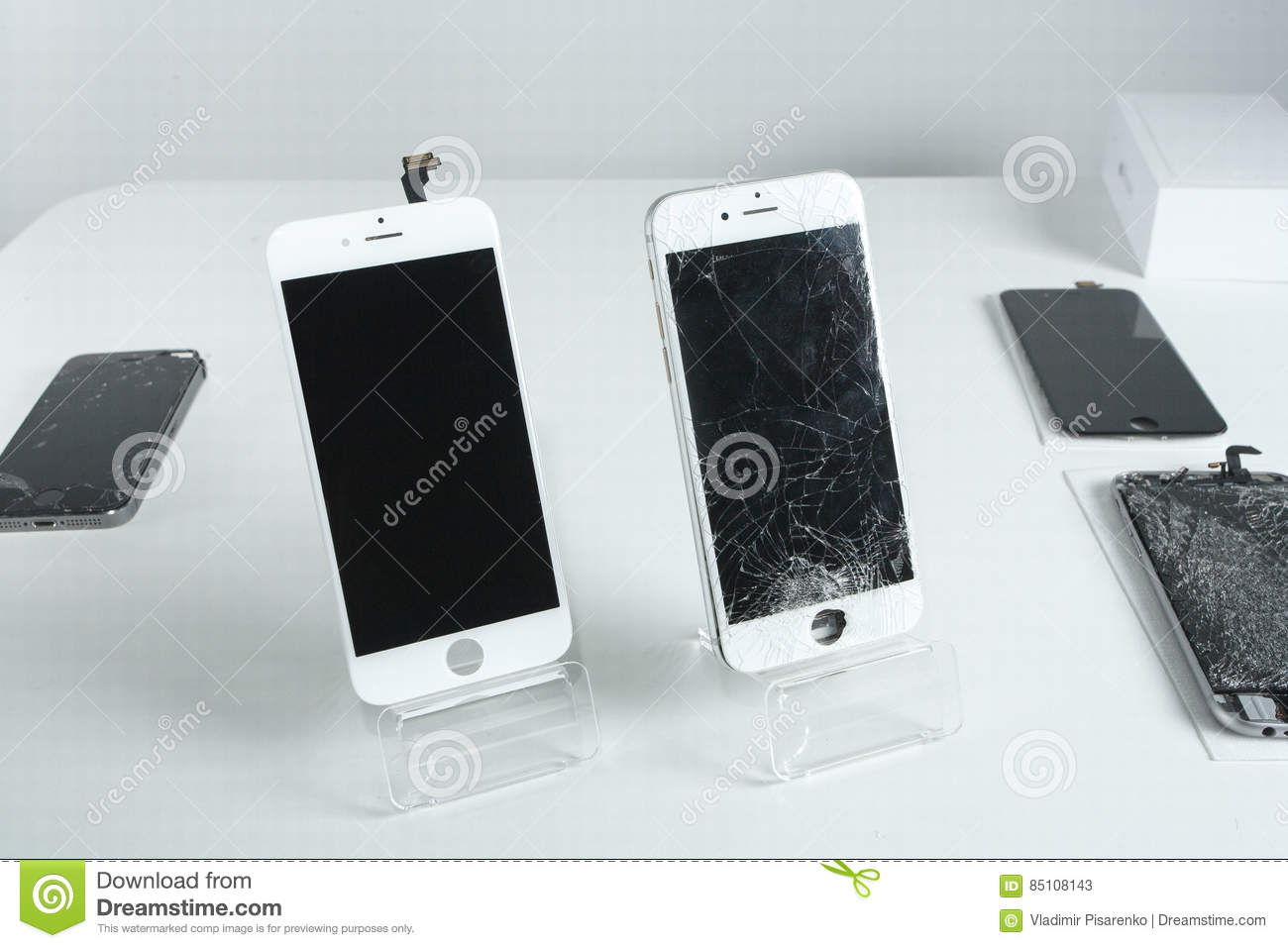 Different modern mobile phones with broken screen on white table