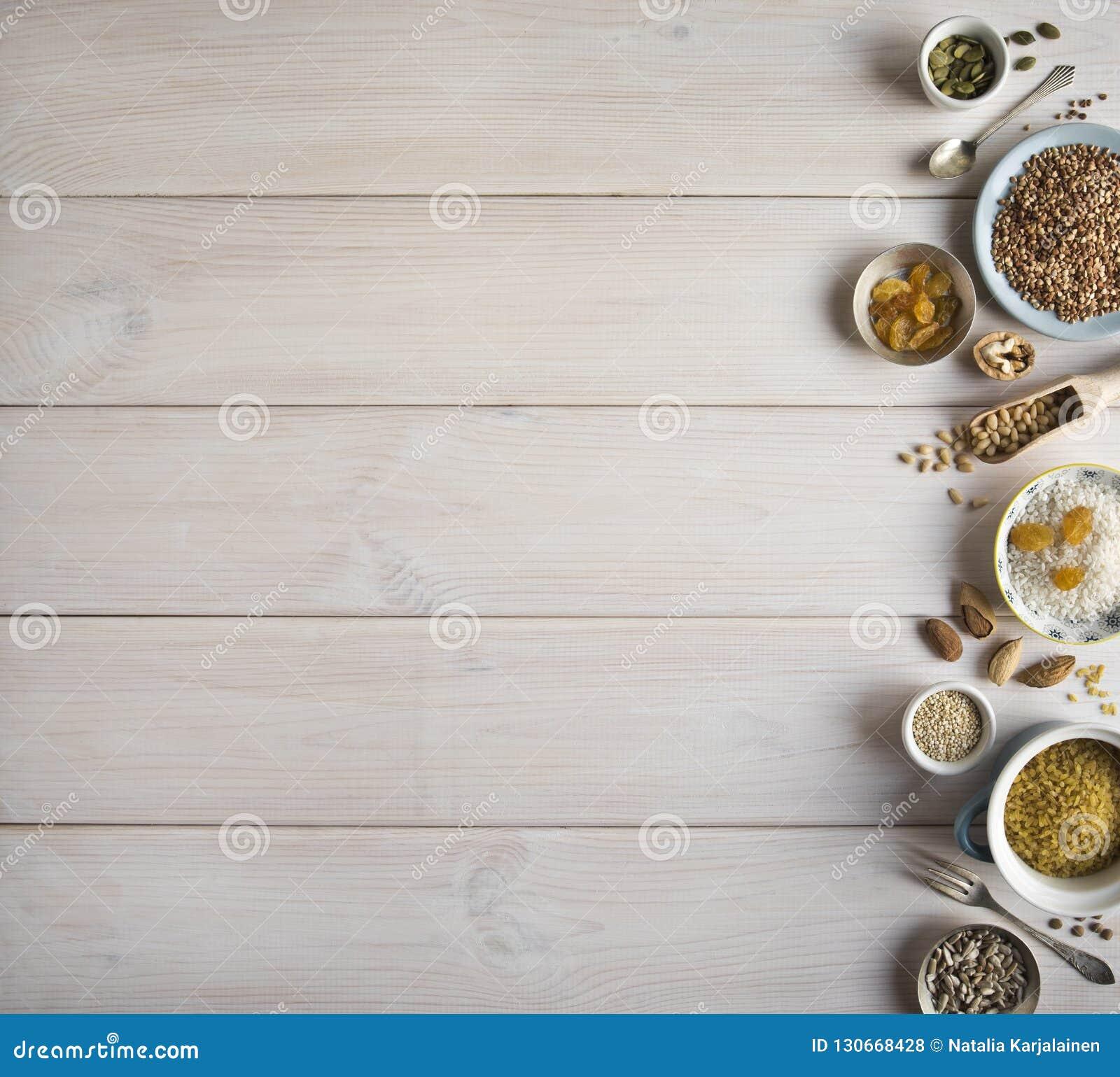 Different nuts, cereals, raisins on plates on a wooden table. Cedar, cashew, hazelnut, walnuts, almonds, pumpkin seeds, sunflower