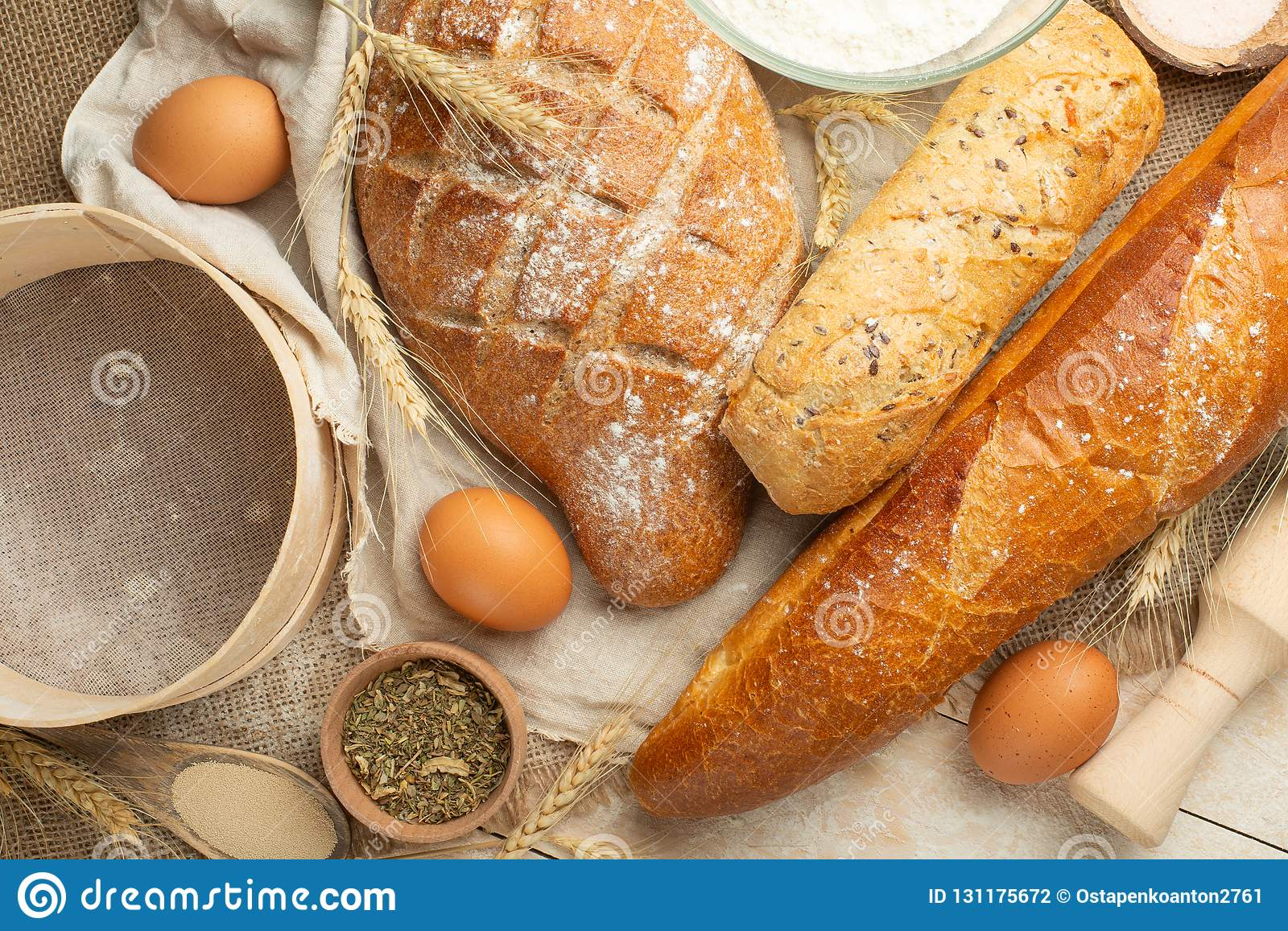Different sorts of bread with wheat and eggs, top view. The concept of a bakery and food store.