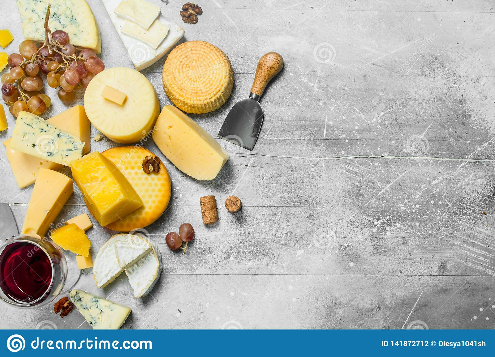 Different types of cheese with grapes, nuts and a glass of red wine