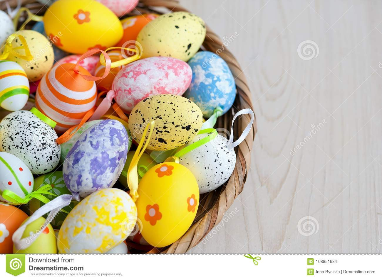 Different Variations Of Easter Eggs In A Wicker Plate On A Light
