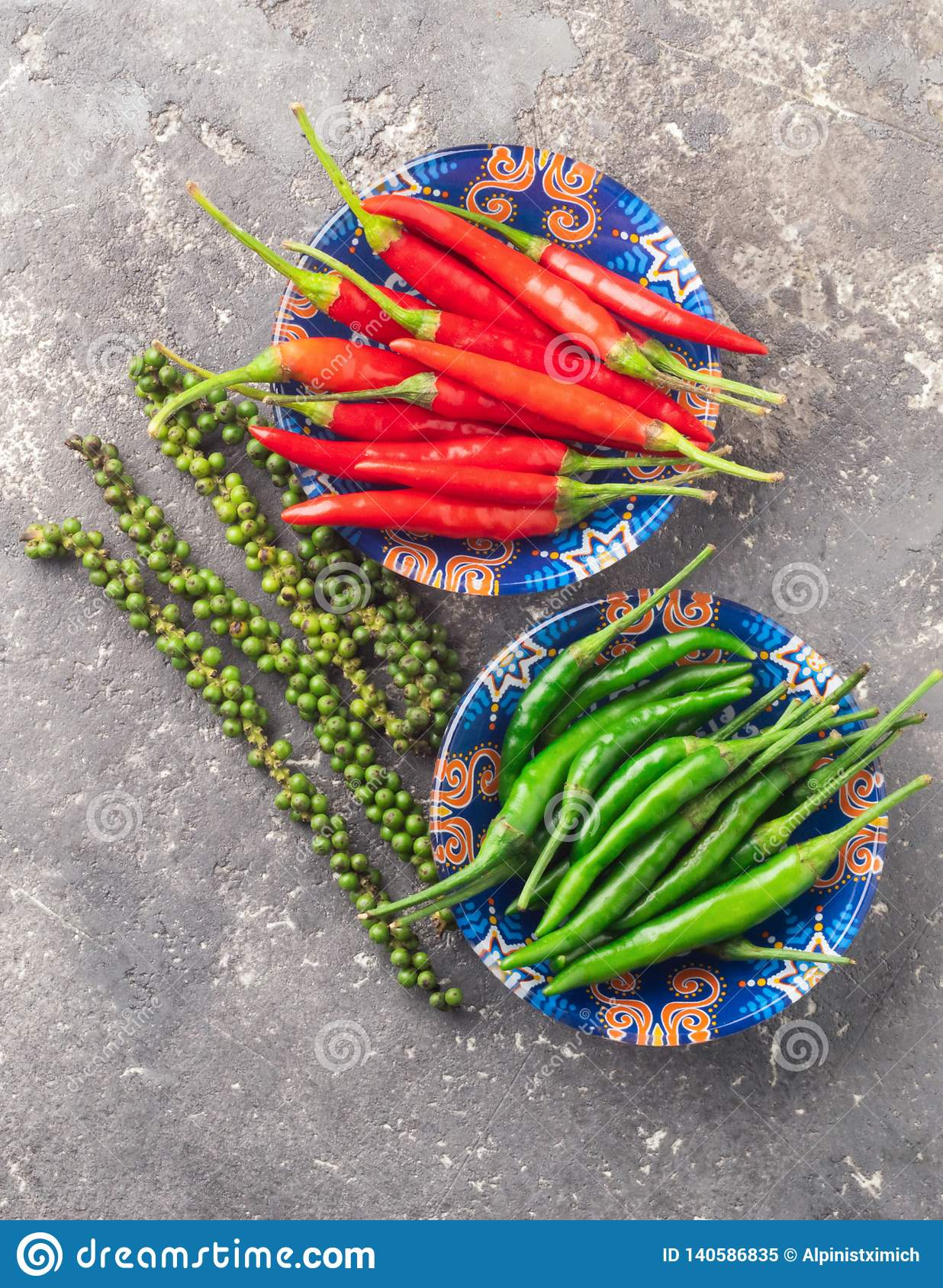 Different varieties of hot pepper on a gray textured background. East Asian food concept. Flat layout.
