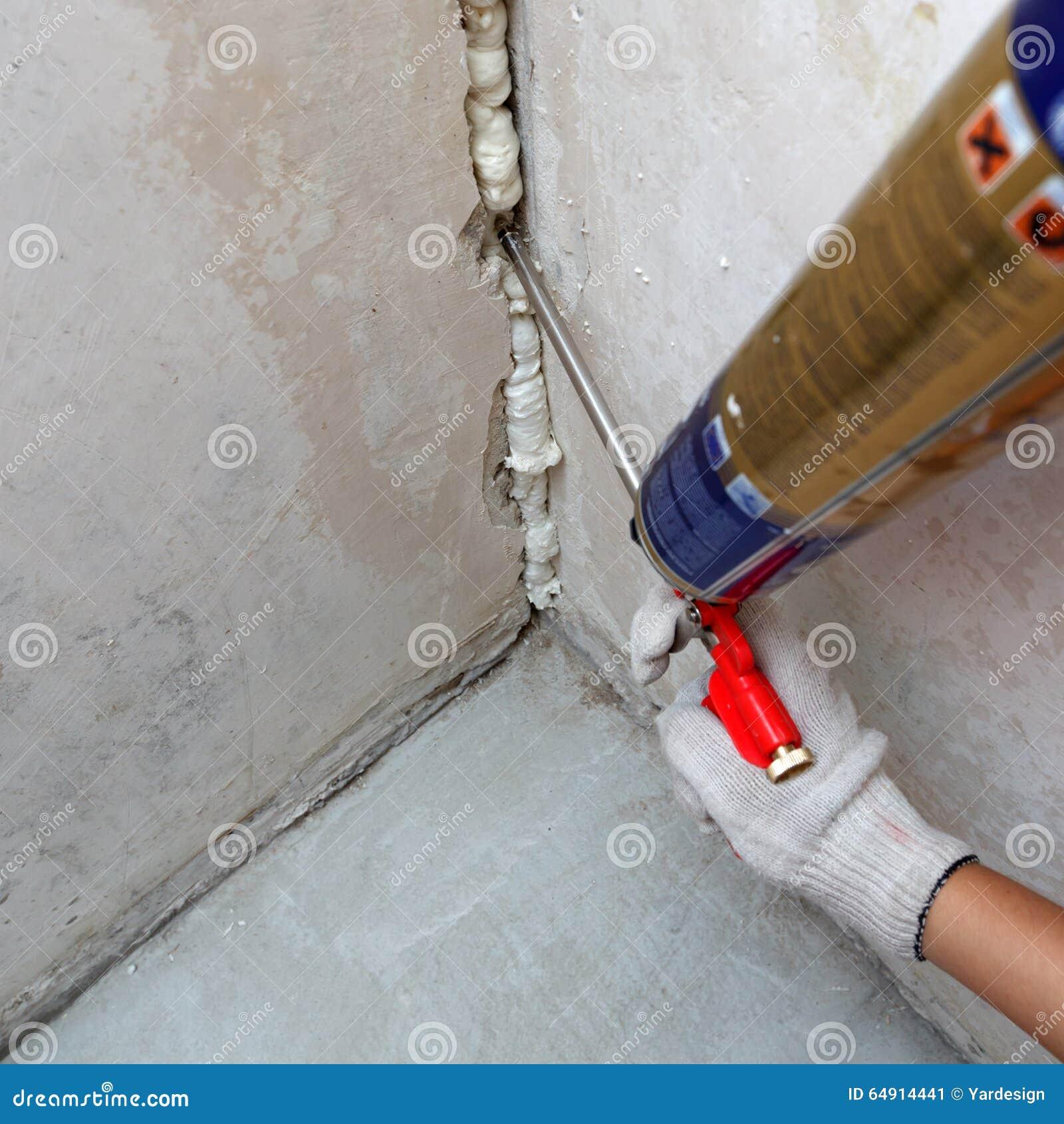 Difficulté de la main du travailleur un loyer dans le mur utilisant la mousse de polyuréthane
