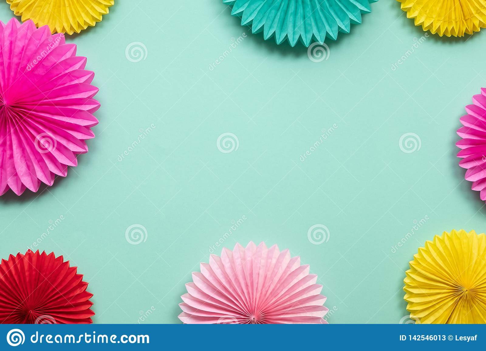 Diffrent paper flowers on green table top view. Festive or party background.  Copy space for text. Birthday greeting card.