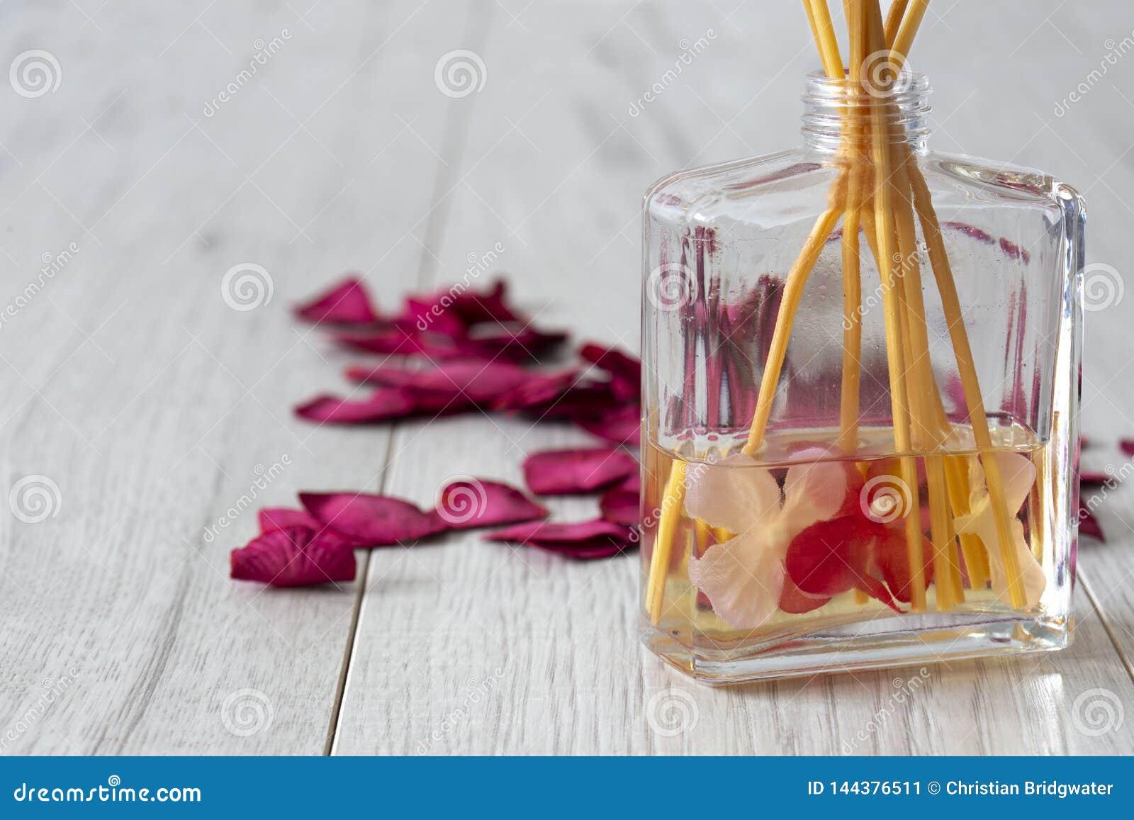 Difusor de Reed con fragancia en un tarro de cristal con los pétalos color de rosa