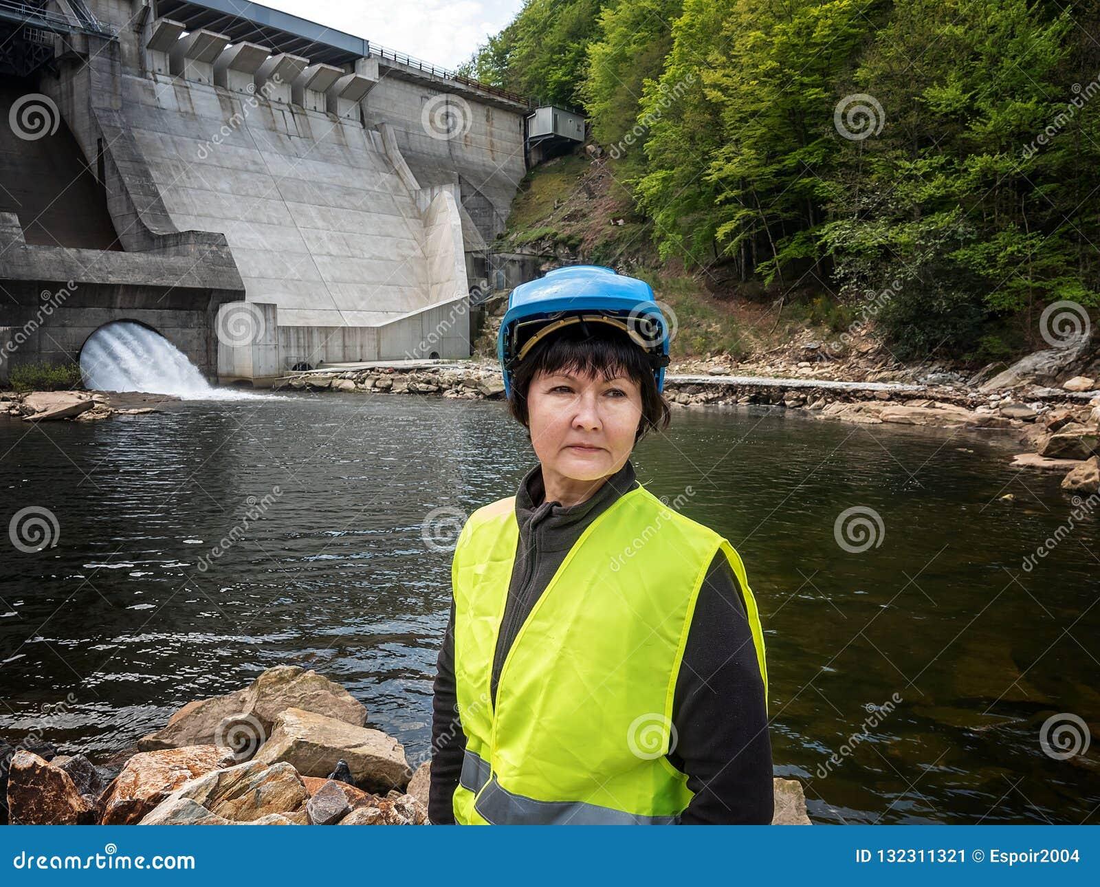 Diga e turbine di una centrale idroelettrica con gli scorrimenti dell acqua di caduta e della donna in casco