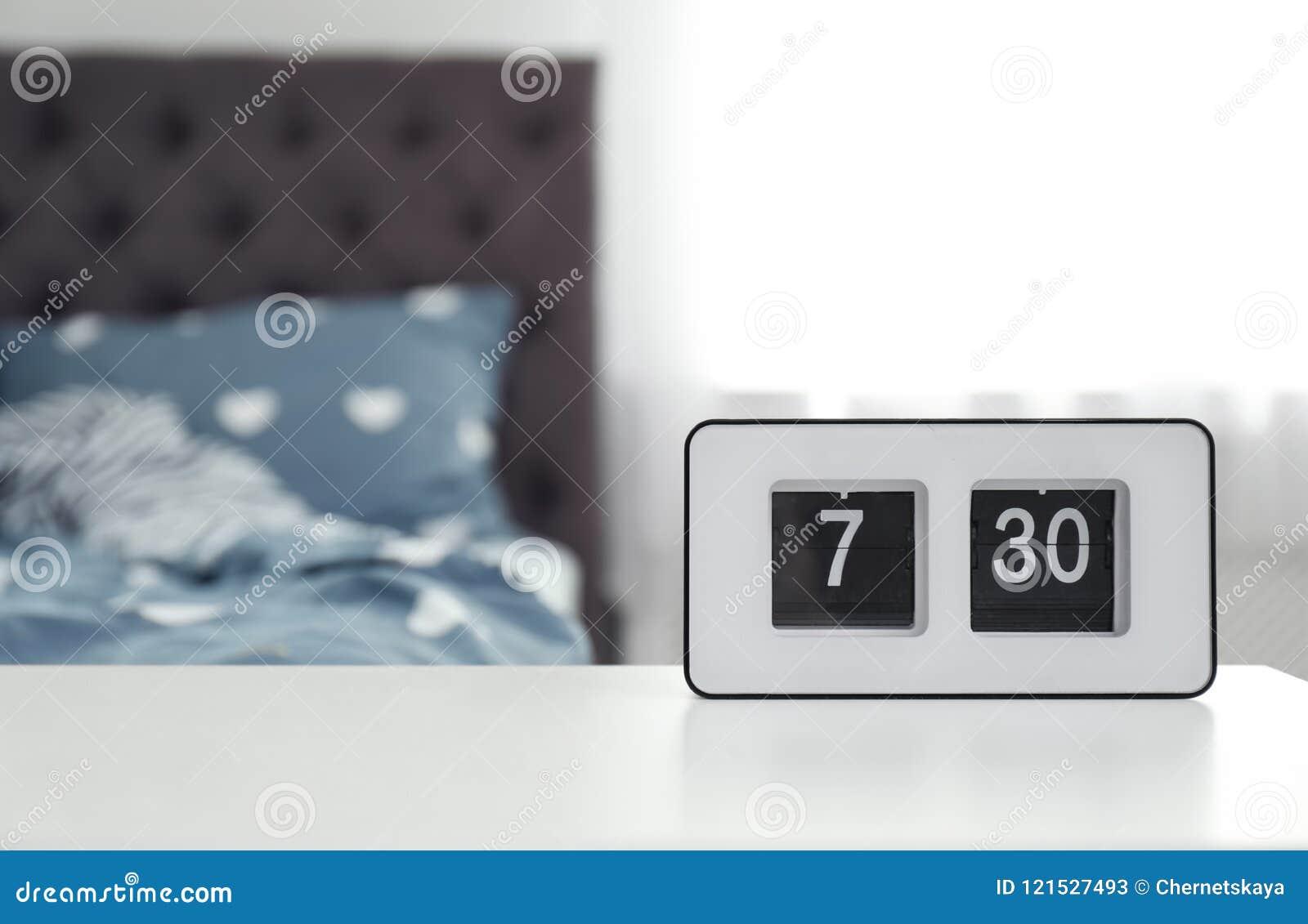 Digital Alarm Clock On Table In Bedroom