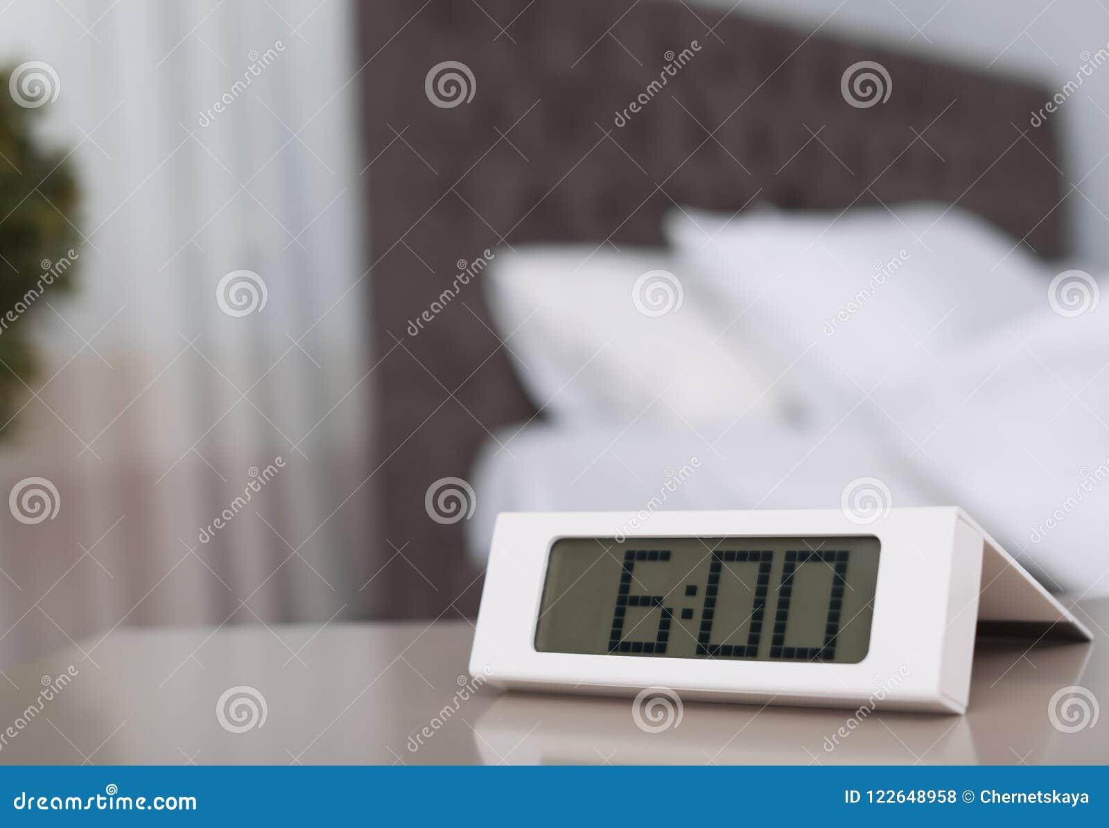 Digital Alarm Clock On Table In Bedroom.