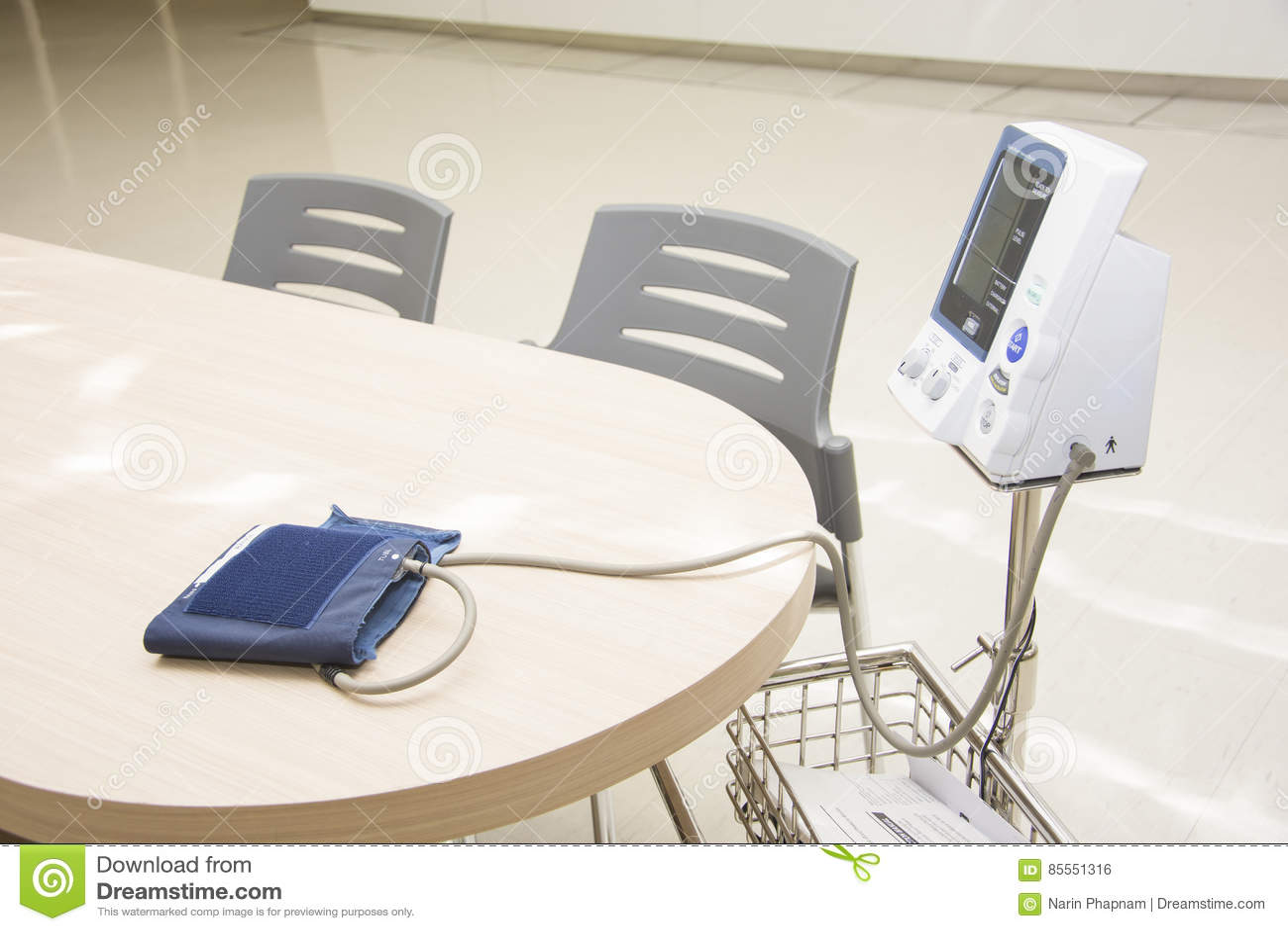 Digital-Blutdruck-Monitorkubikfüße auf dem Schreibtisch