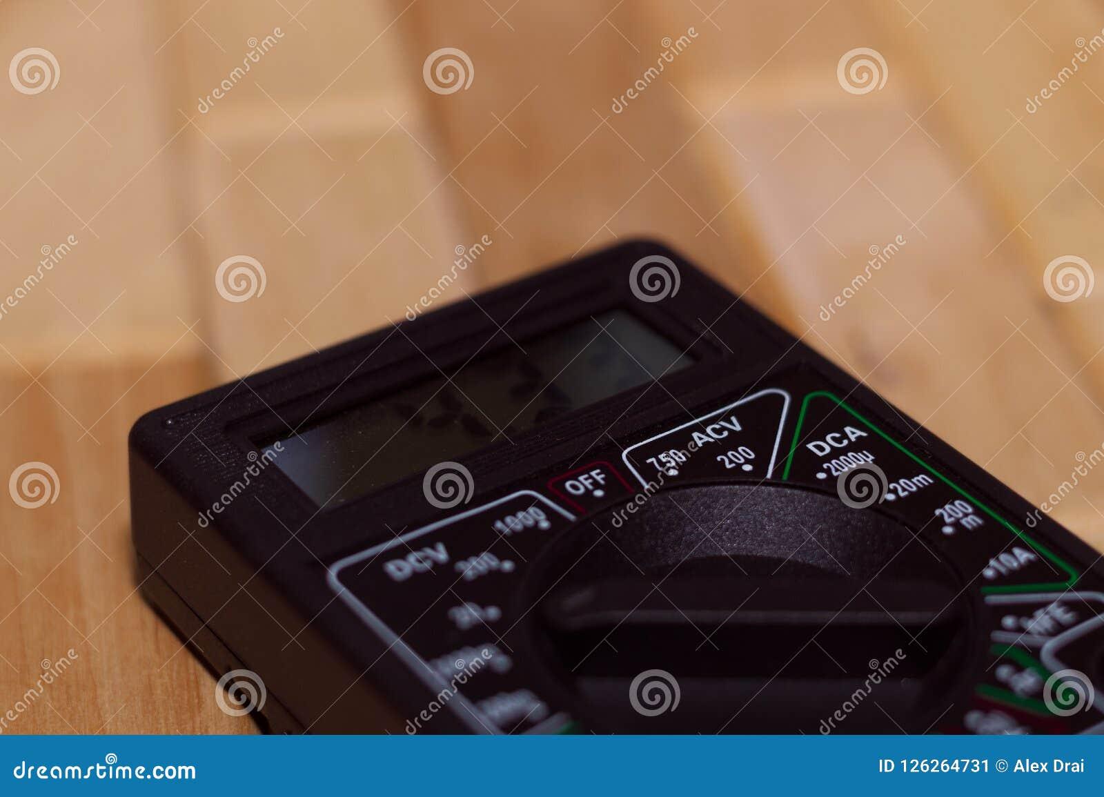 Digital che misura multimetro sul pavimento di legno Mostra 4 33V o batteria completamente caricata Include il voltometro, il amp