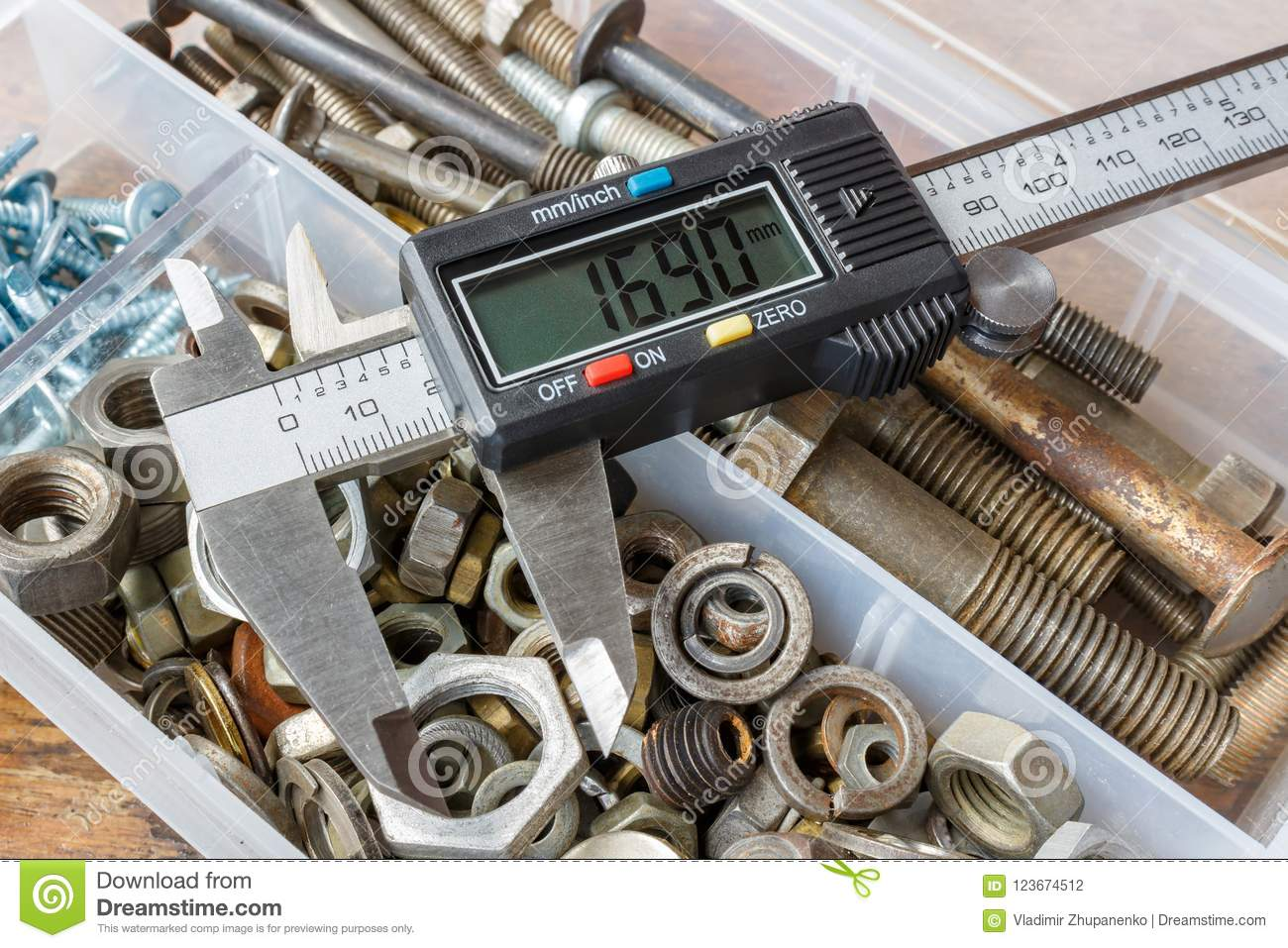Digital electronic caliper on a background of opened storage box with rusty used bolts and nuts