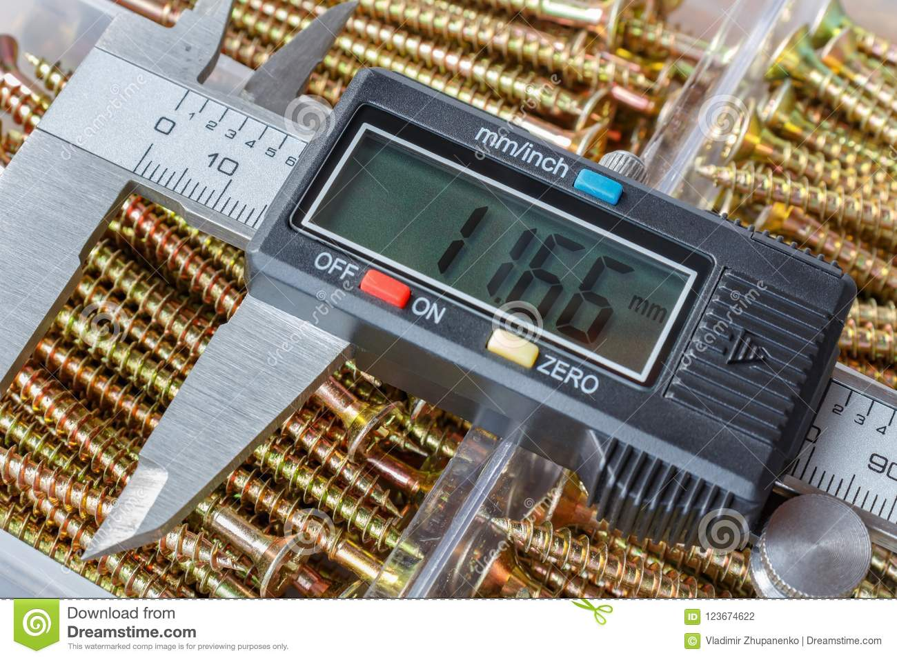 Digital electronic caliper on a background of opened storage box with yellow long screws closeup