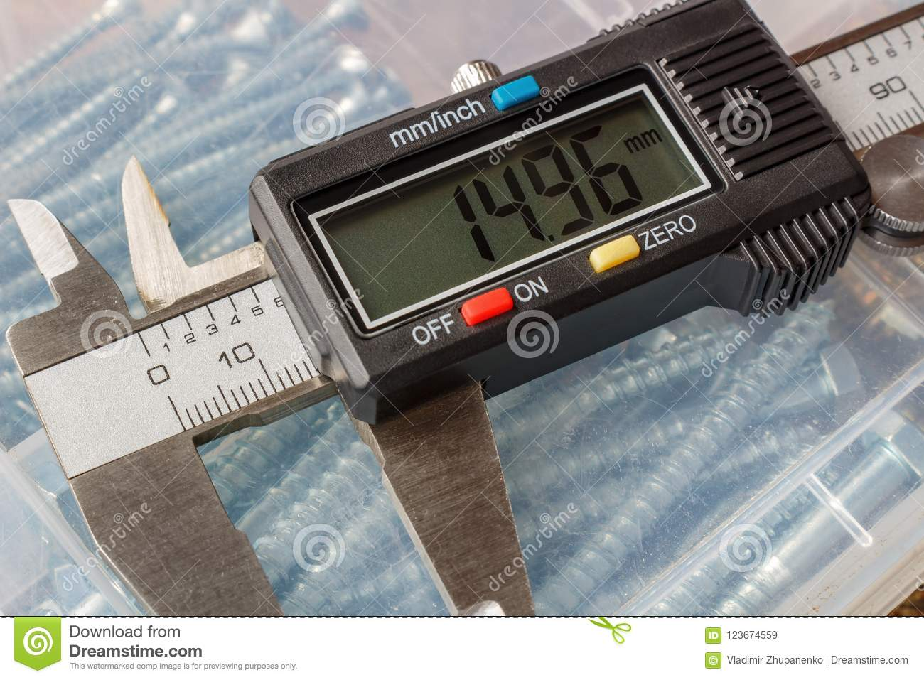 Digital electronic caliper on a background of storage box with hexagon head bolts closeup
