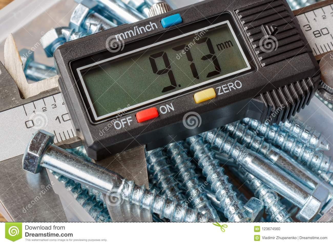 Digital electronic caliper with hexagon head bolts on a background of storage box closeup