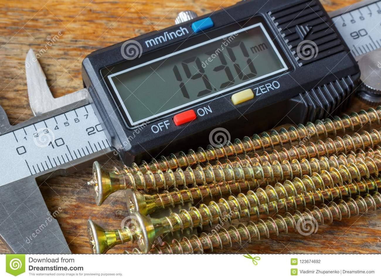 Digital electronic caliper with yellow long screws on wooden table in workshop closeup