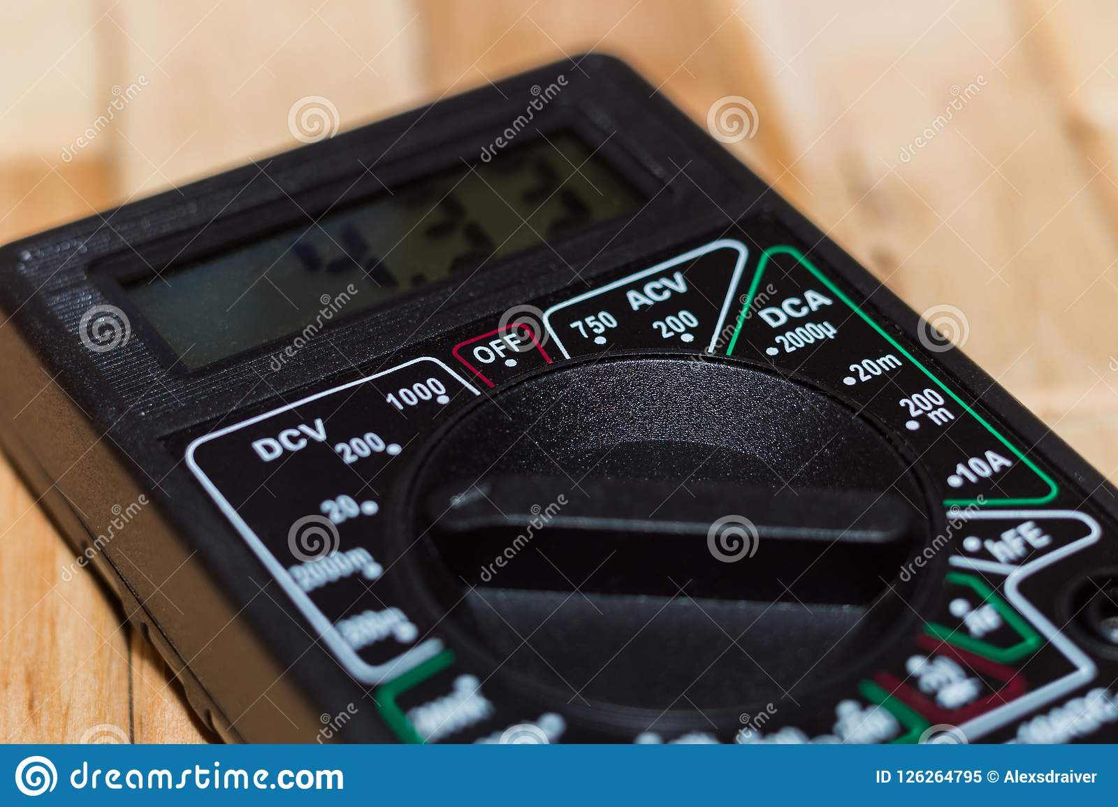 Digital measuring multimeter on wooden floor. It shows 4.33V or fully charged battery. Includes voltmeter, ampermeter, ohmmeter